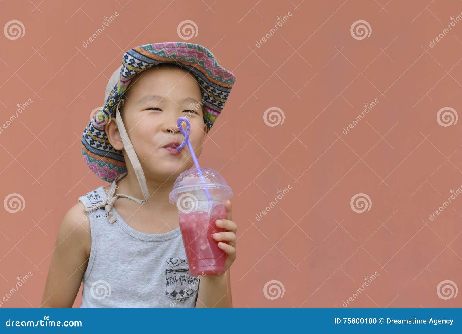 Niño que bebe la bebida fría