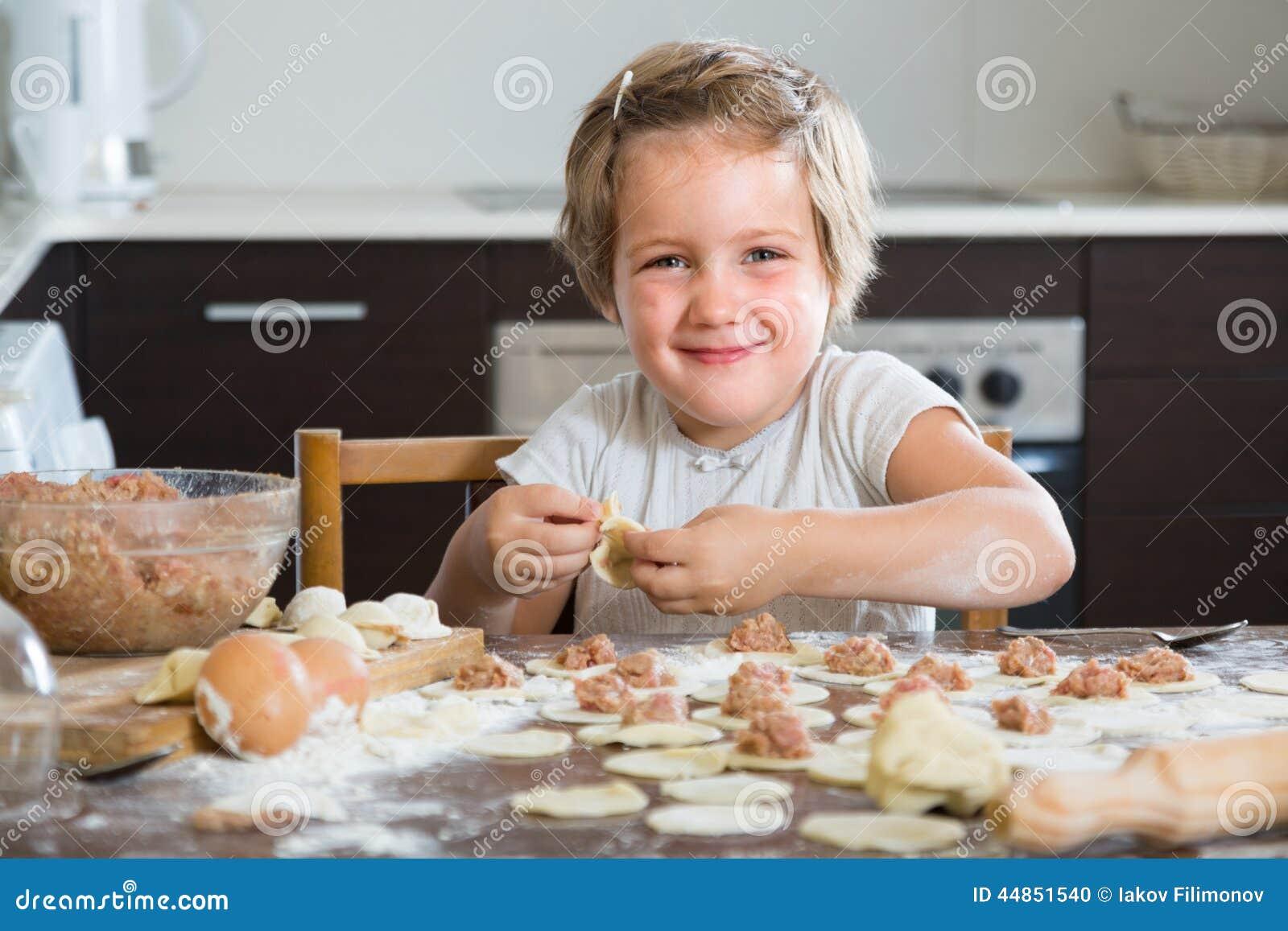 Niño que cocina las bolas de masa hervida de la carne