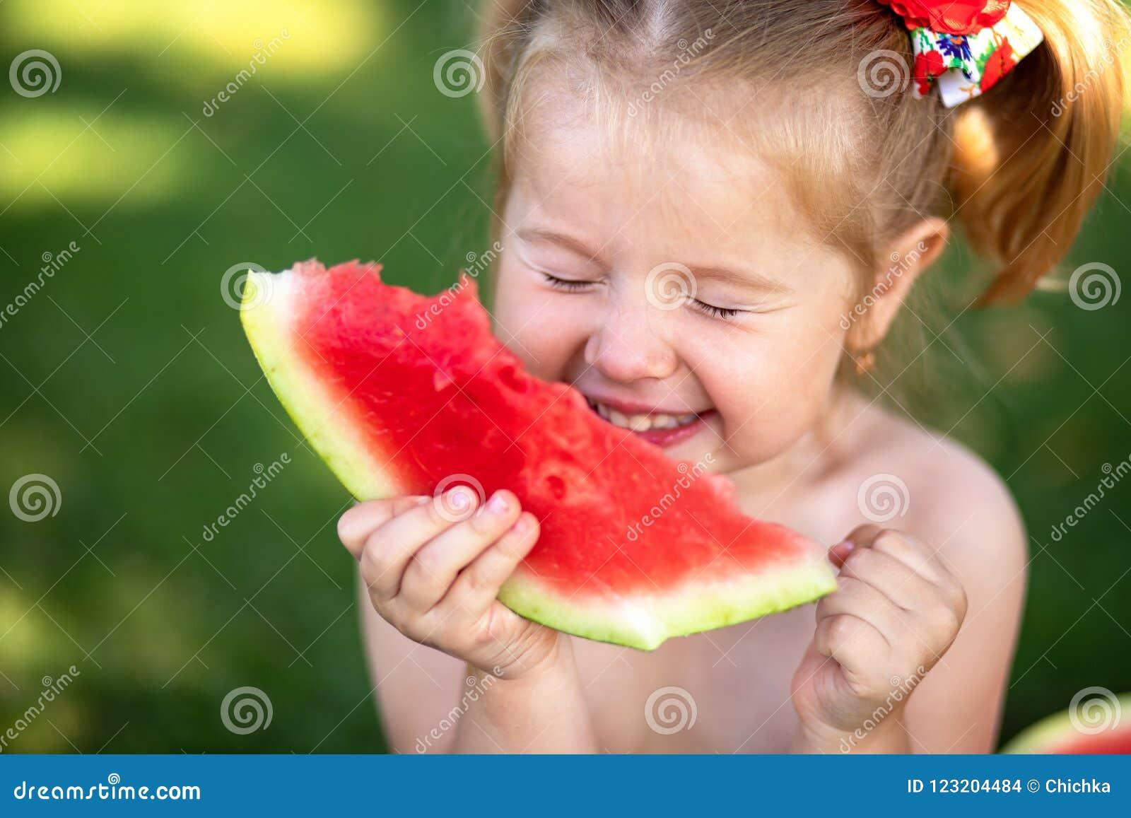 Niño que come la sandía en el jardín Los niños comen la fruta al aire libre Bocado sano para los niños Niña que juega en el contr