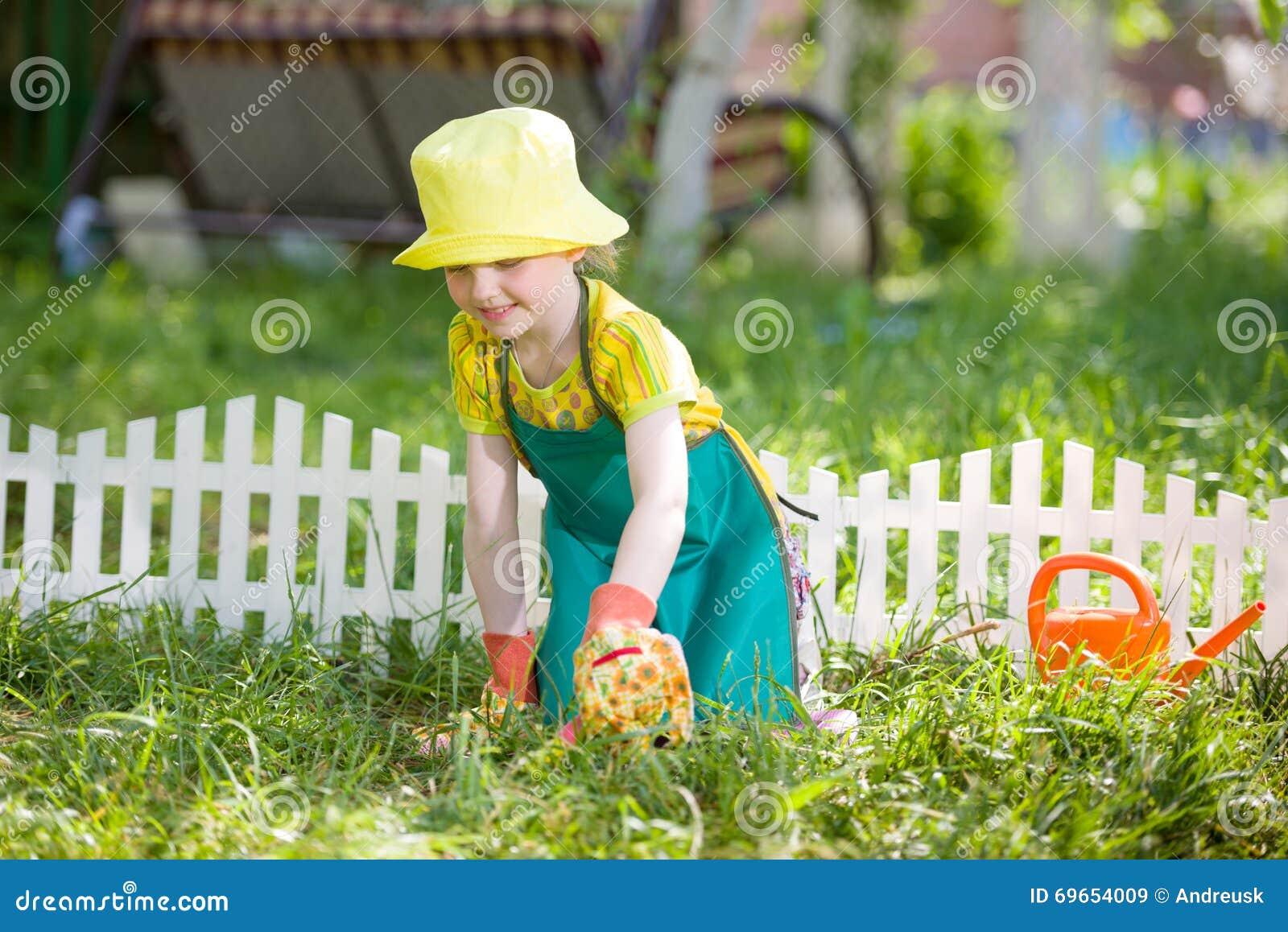 Niño que cultiva un huerto y que riega