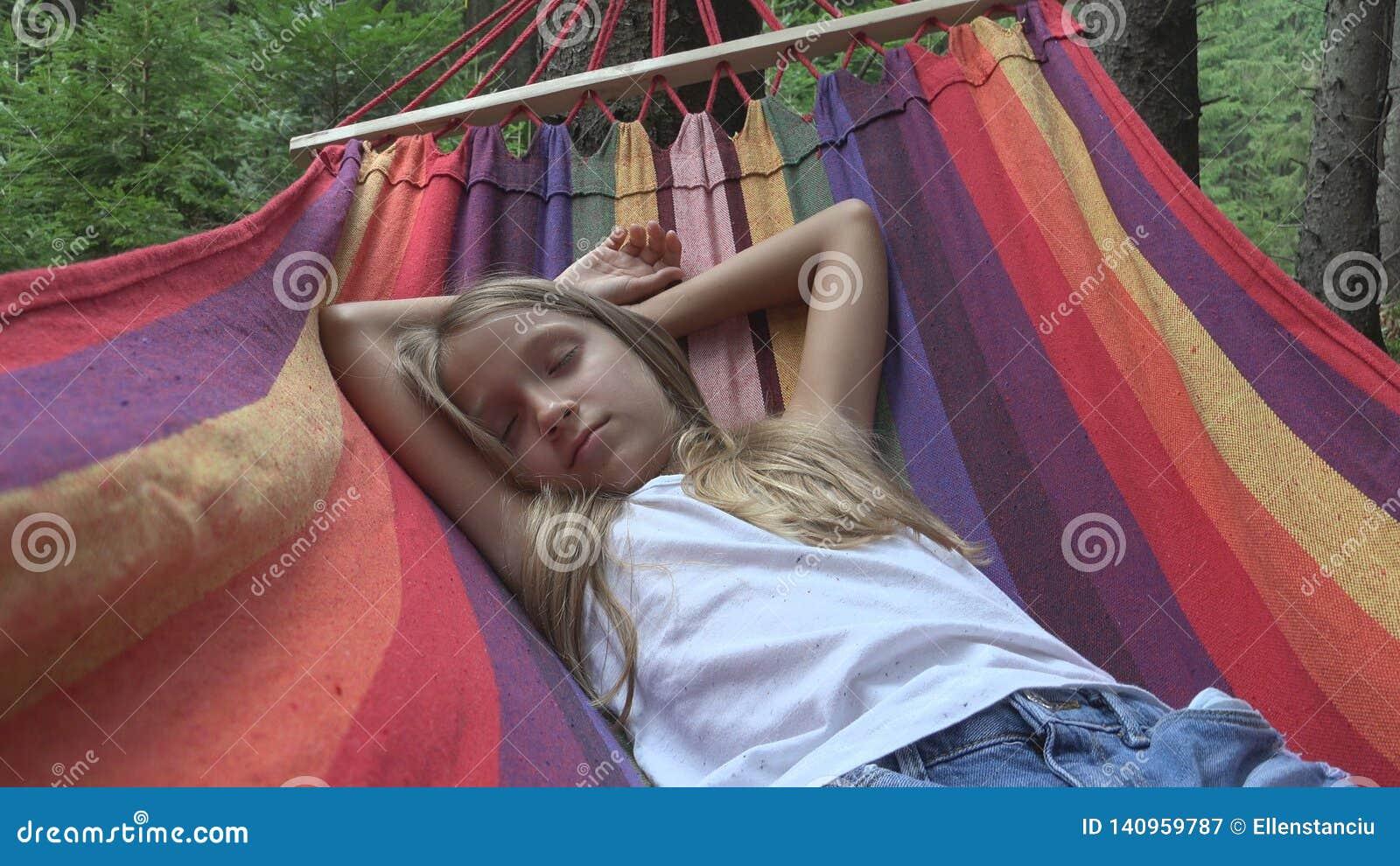 Niño que duerme en hamaca en acampar, niño que se relaja en bosque, muchacha en montañas