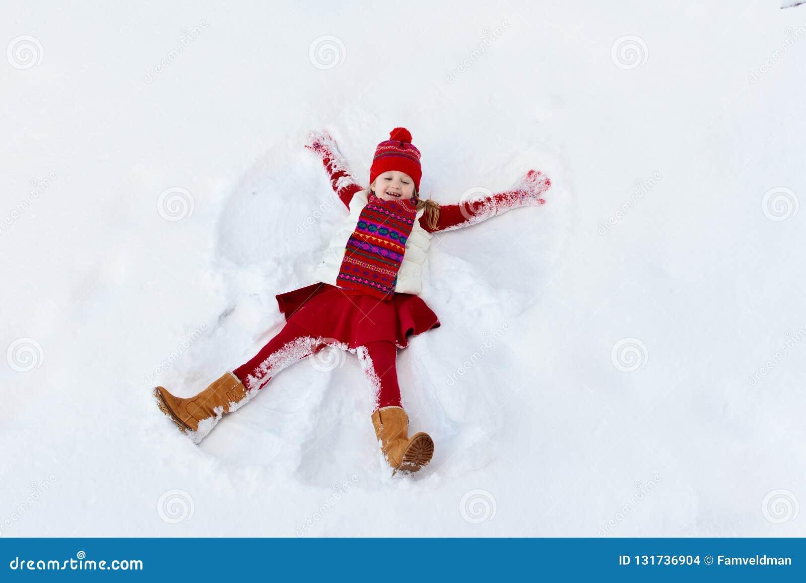 Niño que hace ángel de la nieve en mañana soleada del invierno Diversión al aire libre del invierno de los niños Vacaciones de la