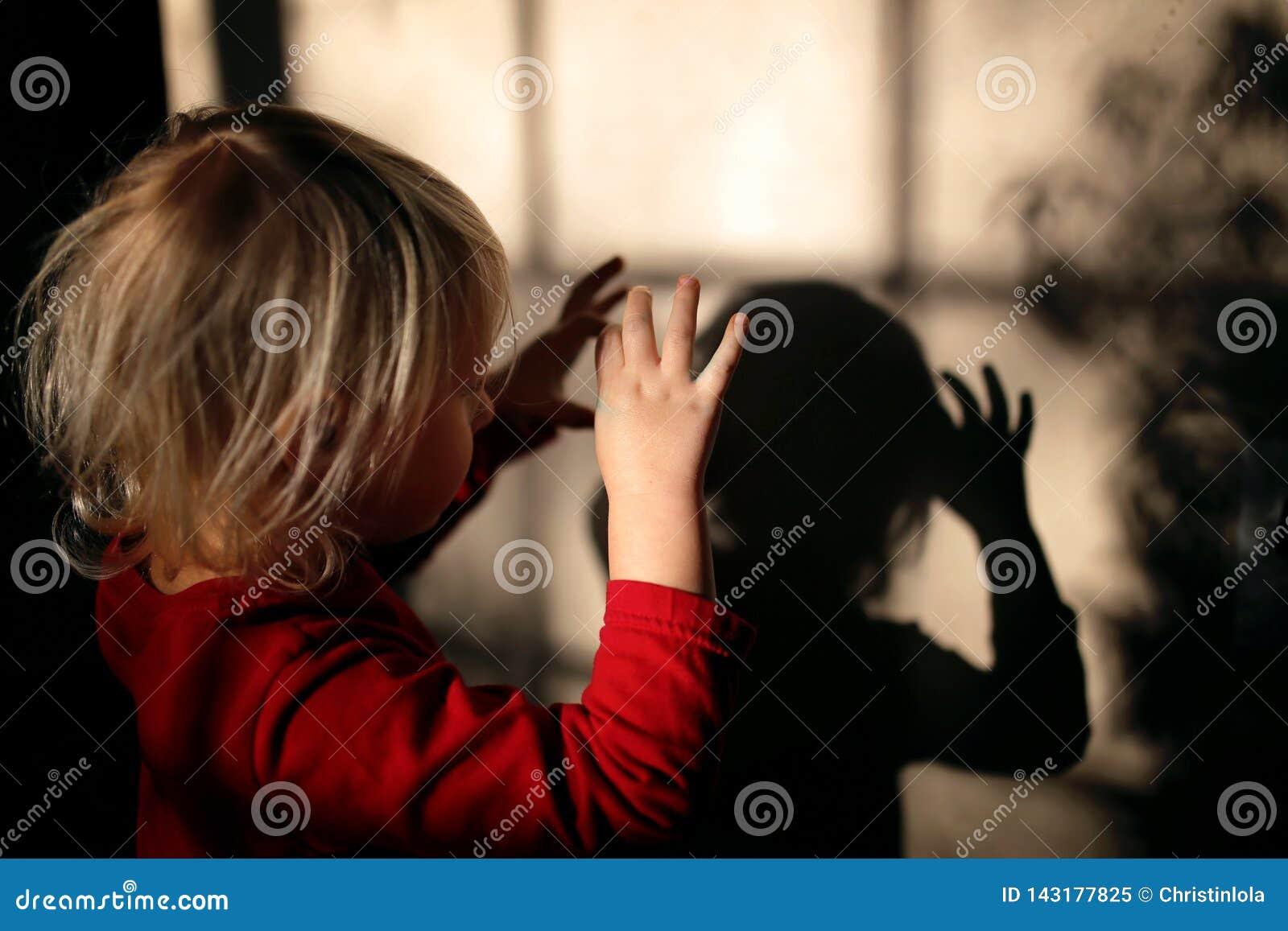 Niño que hace marionetas de la sombra con los fingeres en la pared de su hogar