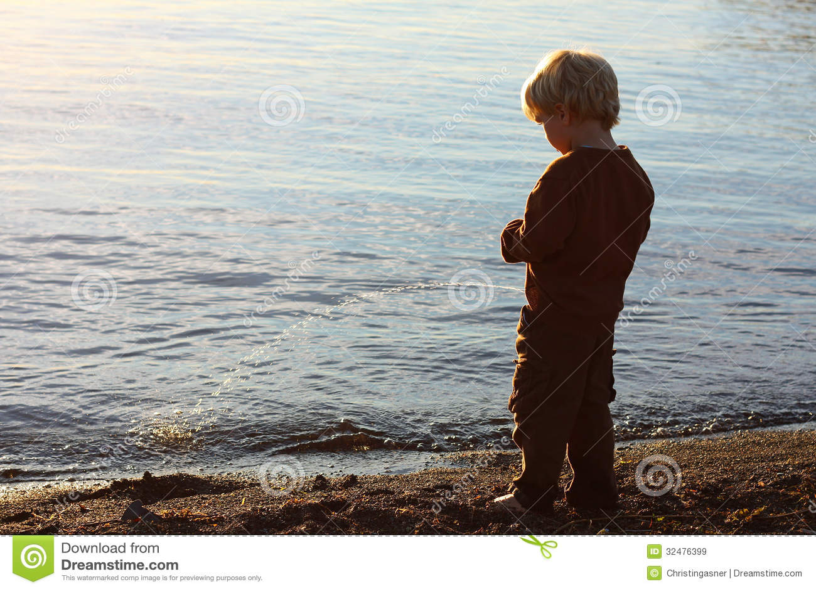 Un niño joven del muchacho tiene el suyo de nuevo a la cámara y se ...: http://es.dreamstime.com/im%C3%A1genes-de-archivo-libres-de-regal%C3%ADas-ni%C3%B1o-que-hace-pis-en-la-playa-image32476399