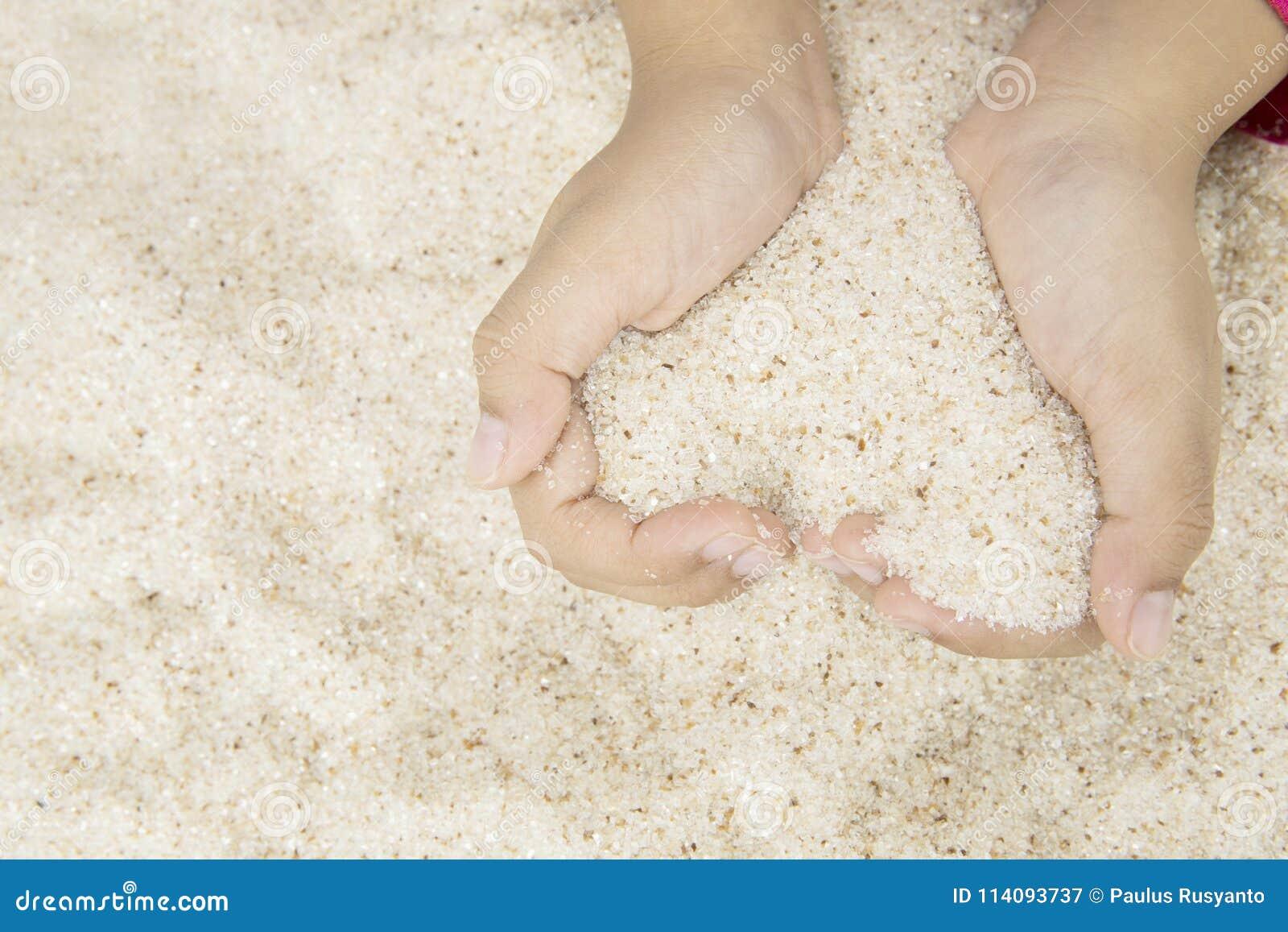 Niño que hace símbolo del corazón de la arena de la playa