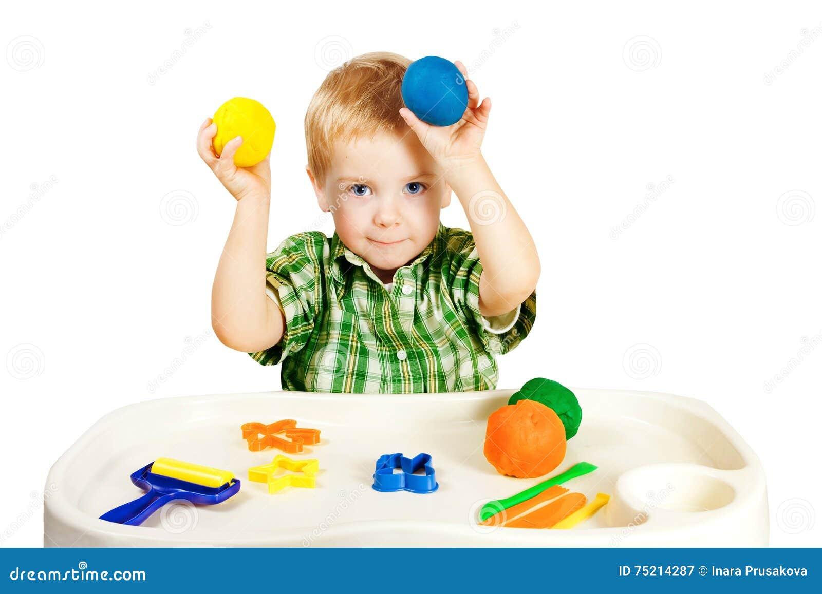 Niño que juega a Clay Toys que moldea, plastilina colorida del pequeño niño