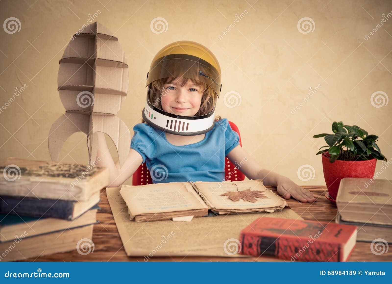 Niño que juega con el cohete del juguete de la cartulina
