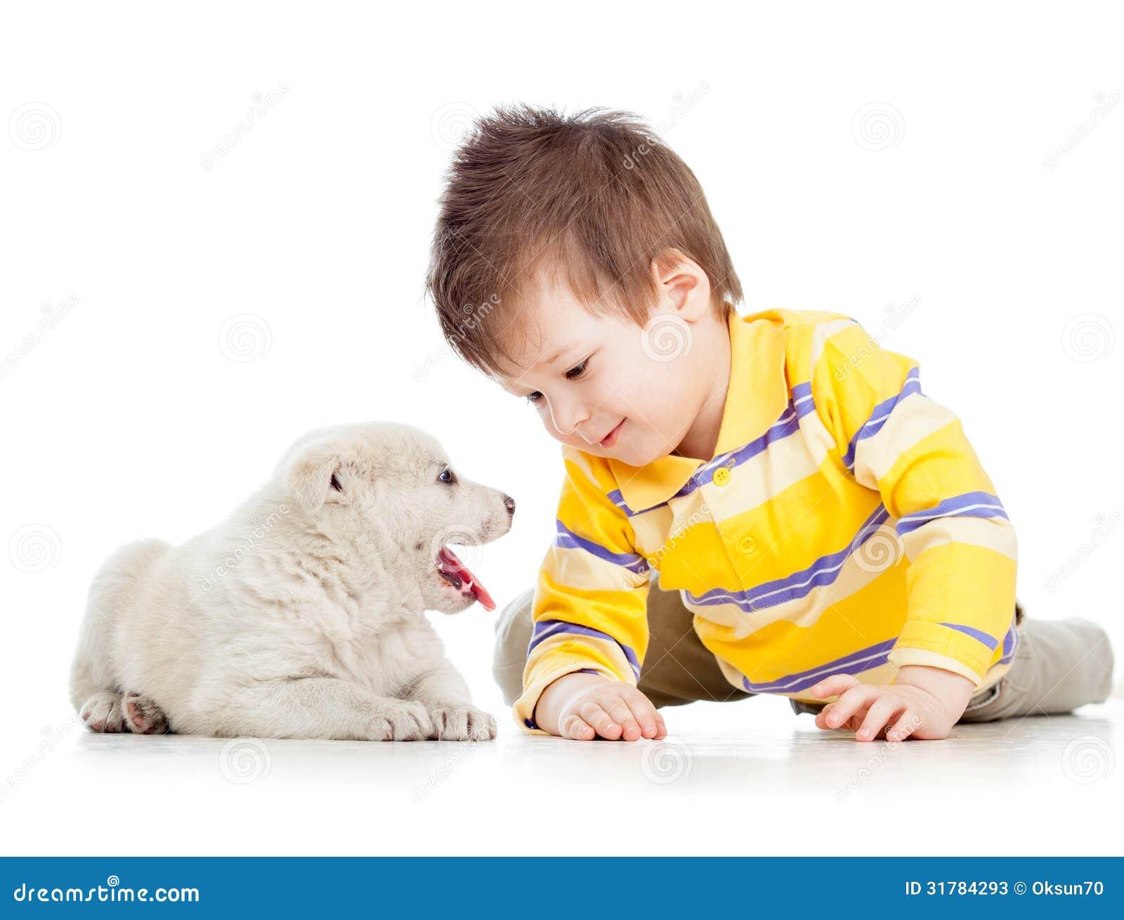 Niño que juega con el perro de perrito