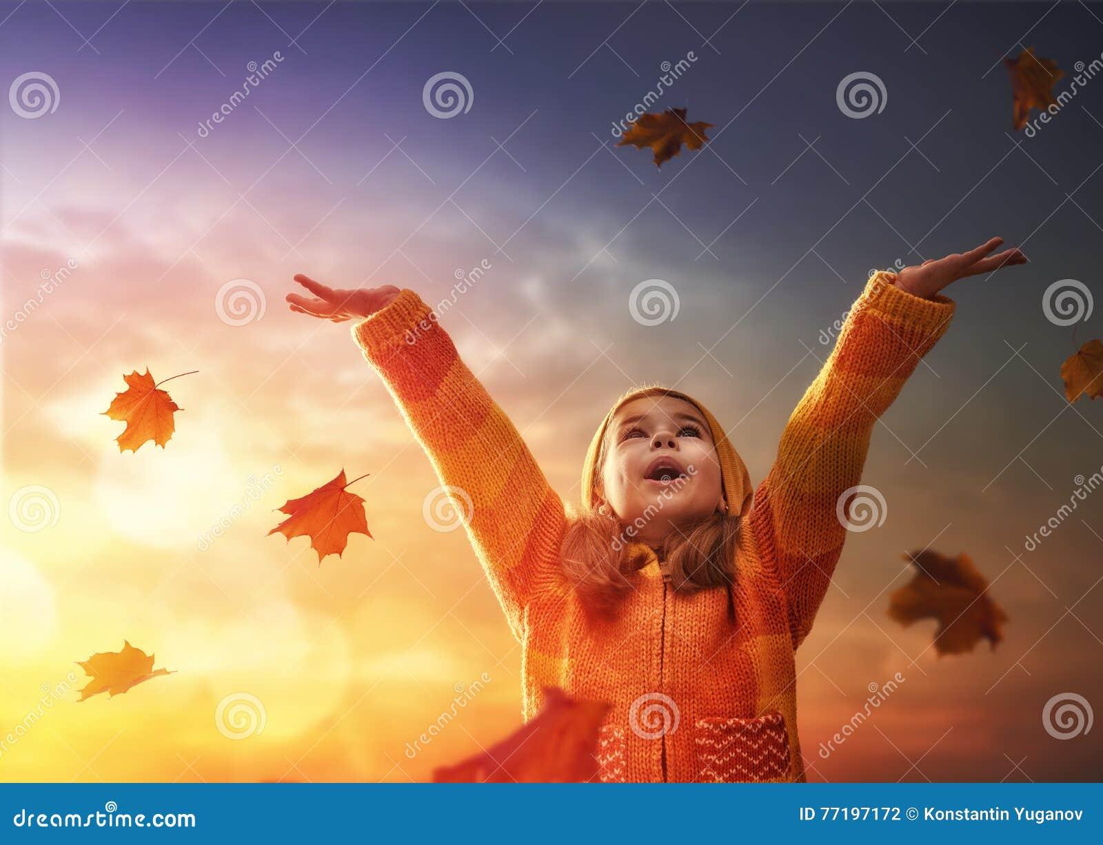 Niño que juega en el otoño