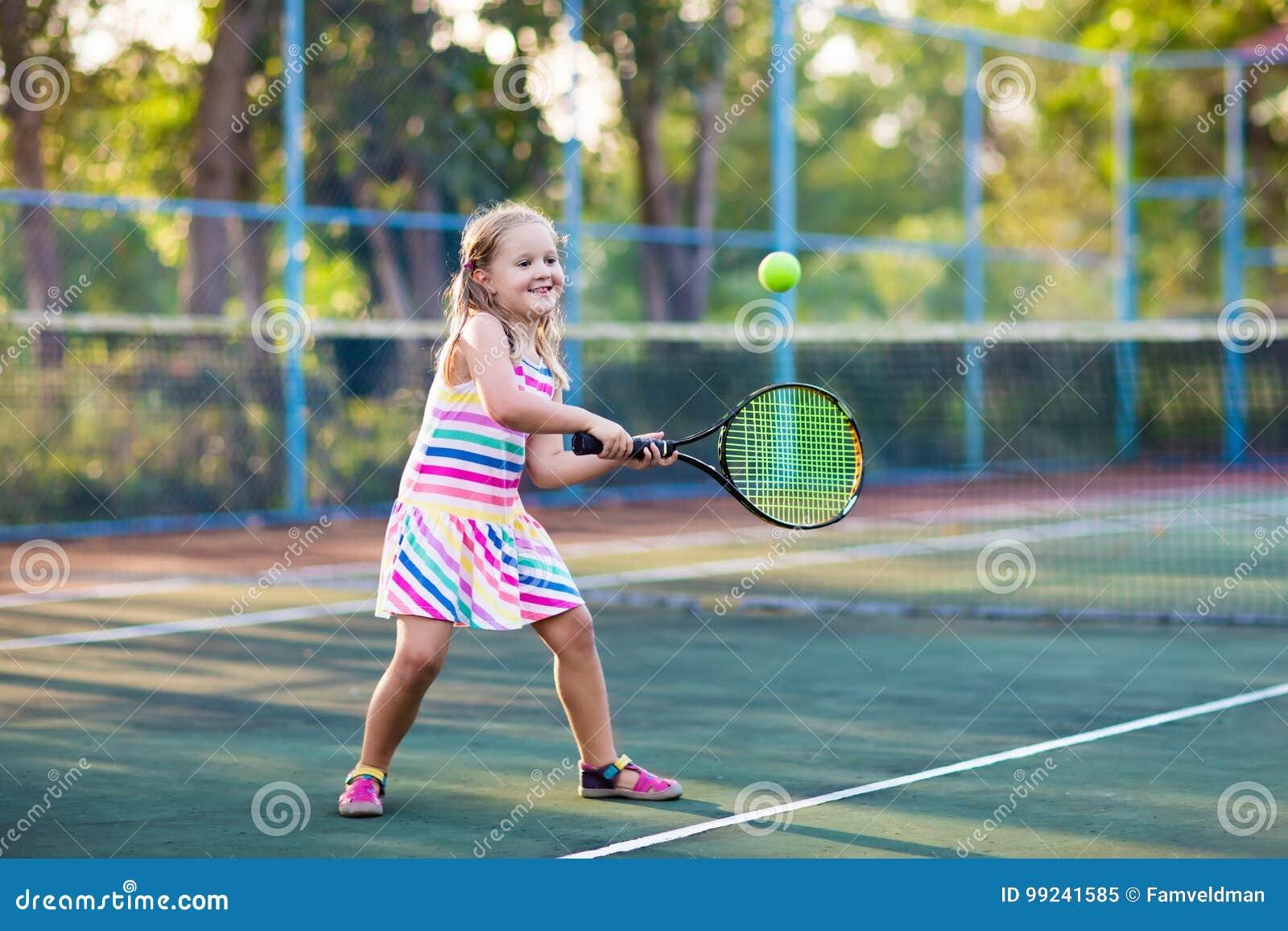Niño que juega a tenis en corte al aire libre