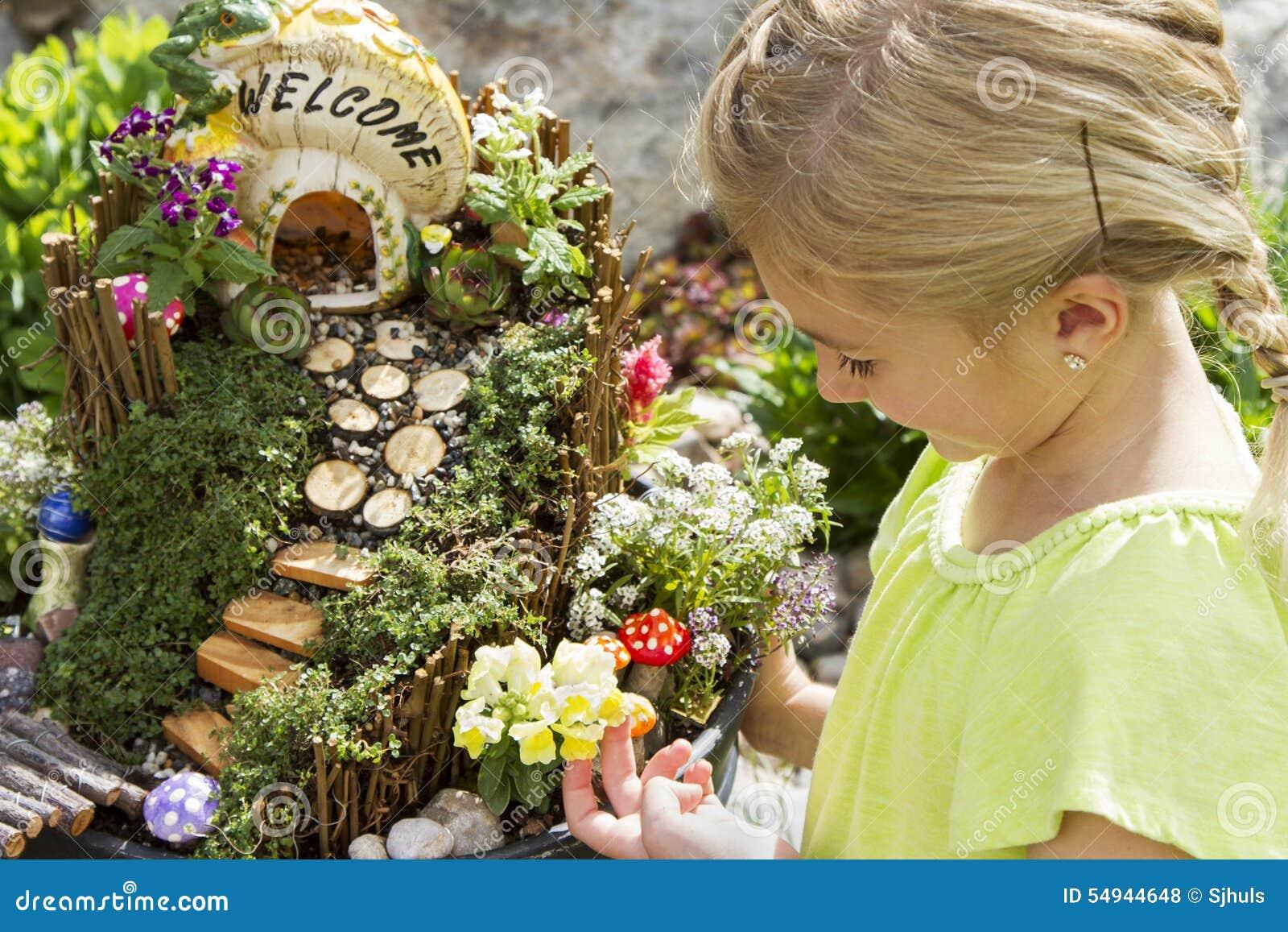 Niño que mira el jardín de hadas en una maceta al aire libre