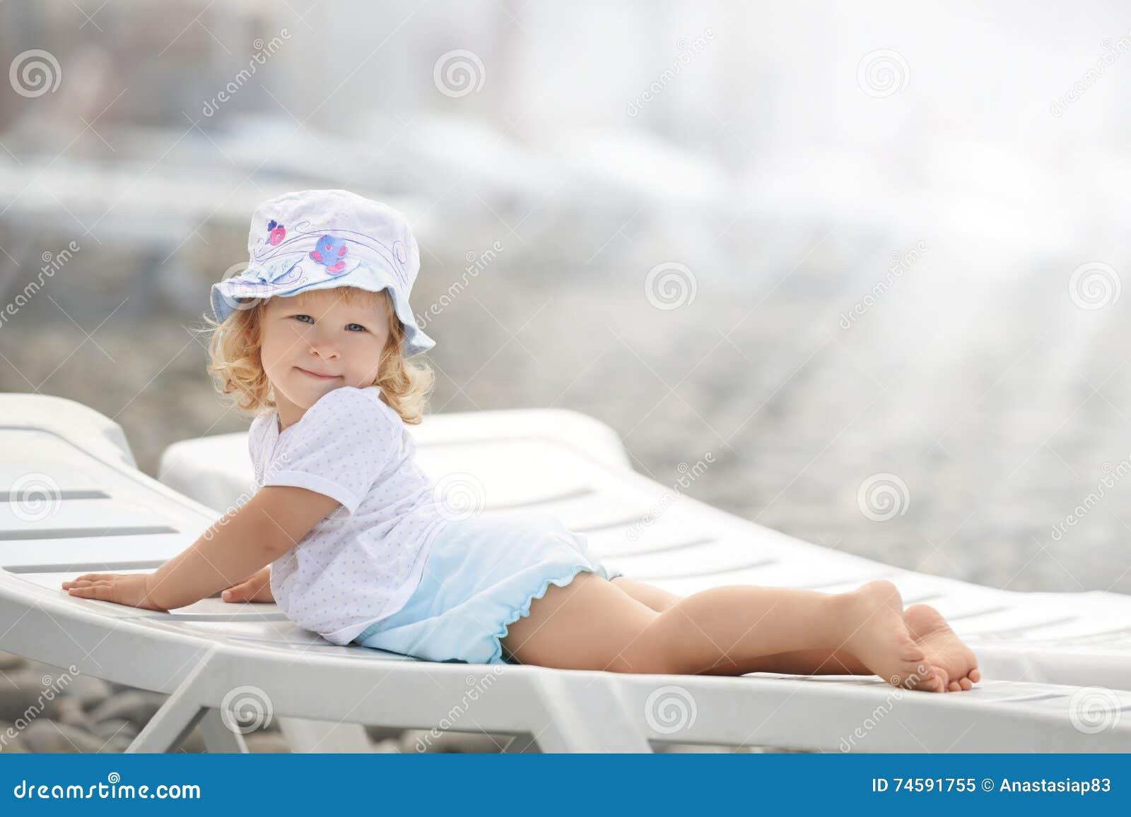 Niño que pone en la calesa de la playa de largo en la luz del sol