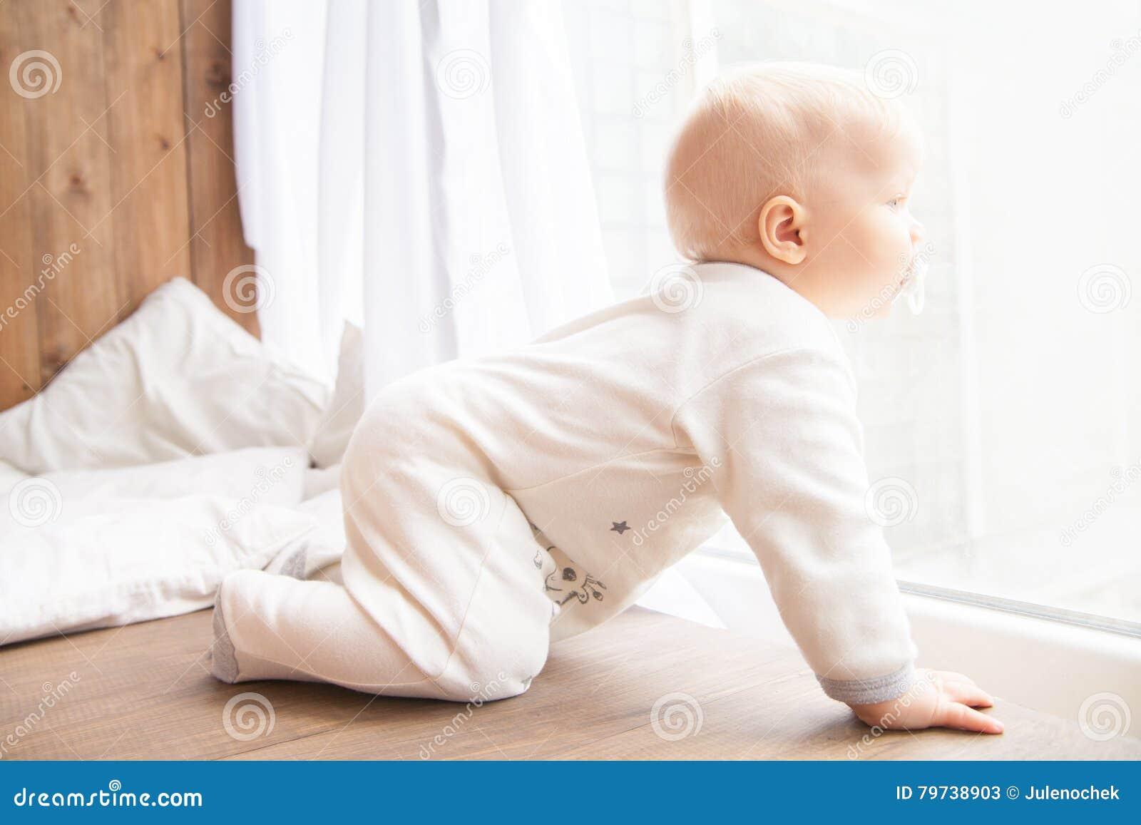 Niño que se arrastra en el sitio blanco
