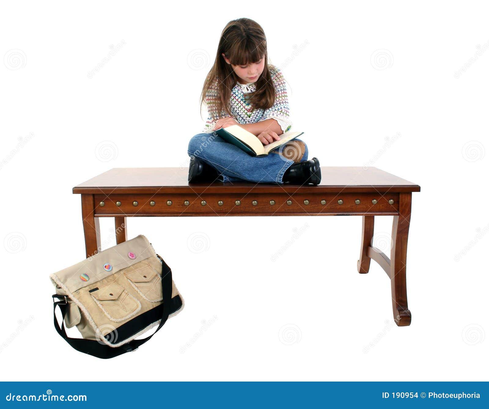 Niño que se sienta en el libro de lectura del vector