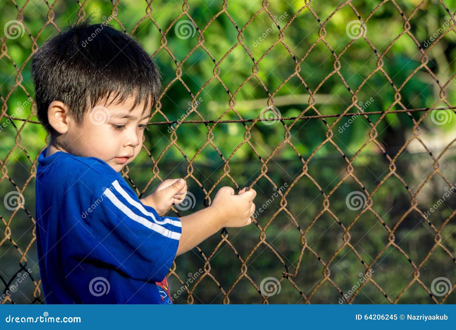 Niño que sostiene la cerca al aire libre