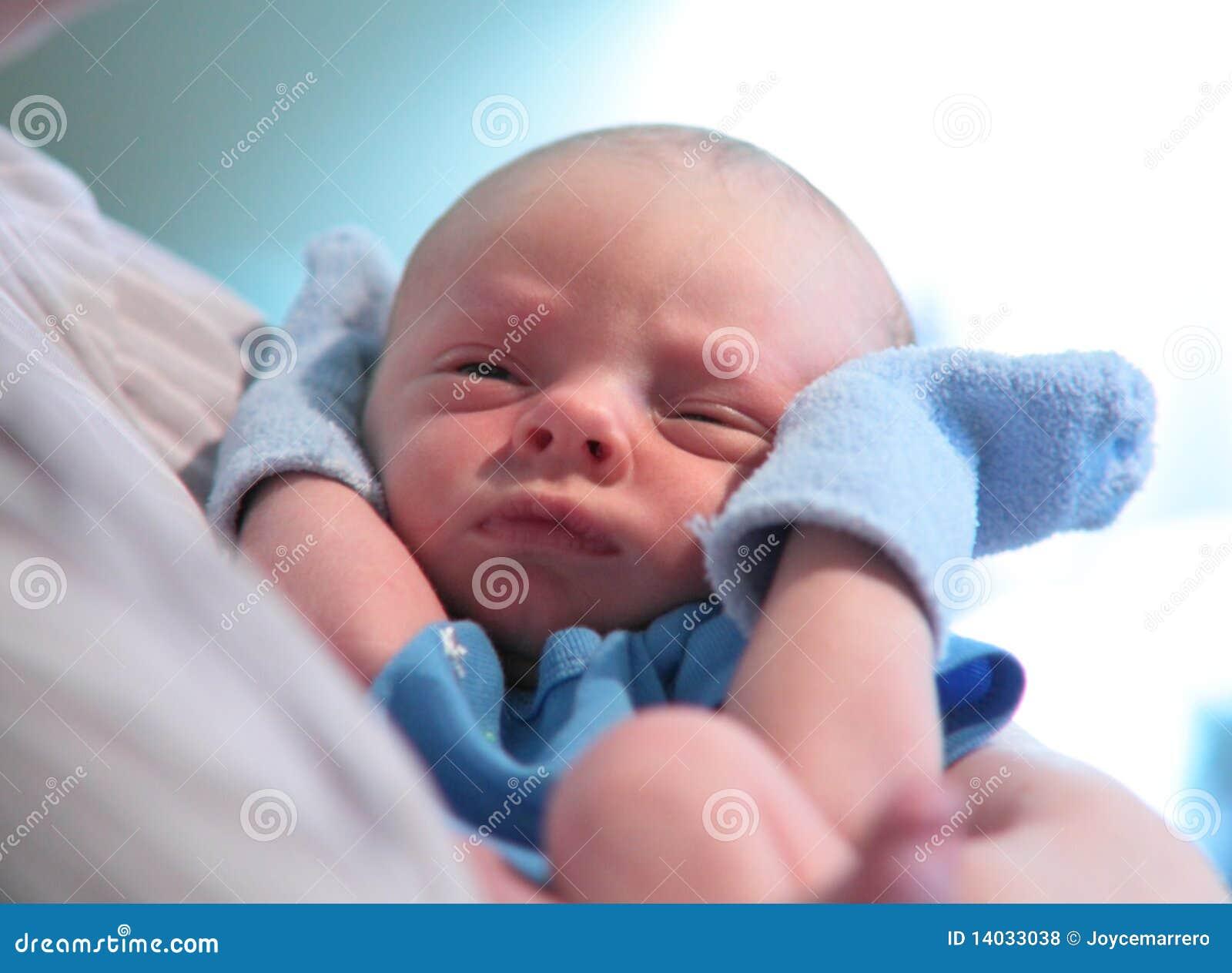 Niño recién nacido con las manoplas