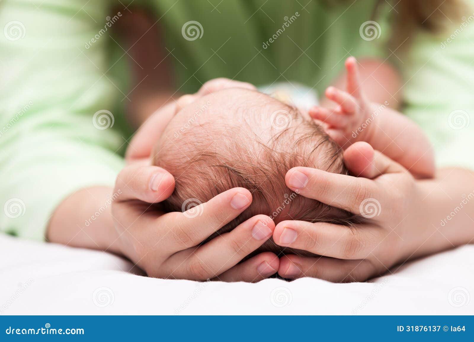 Niño recién nacido durmiente lindo del bebé en las manos de la madre