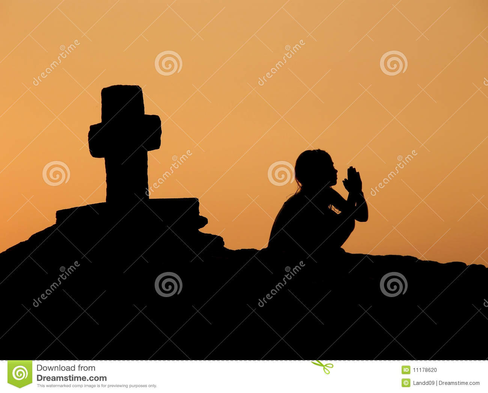 Niño, rezo, cruz en puesta del sol