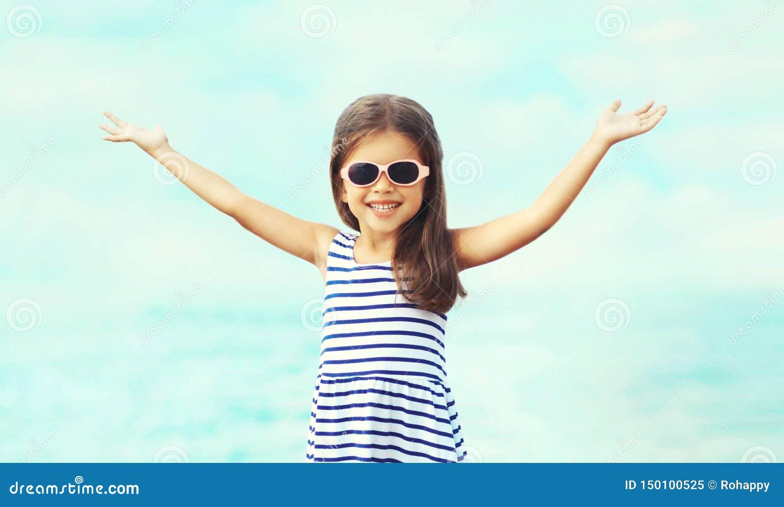 Niño sonriente feliz del primer del retrato del verano que aumenta las manos encima del divertirse