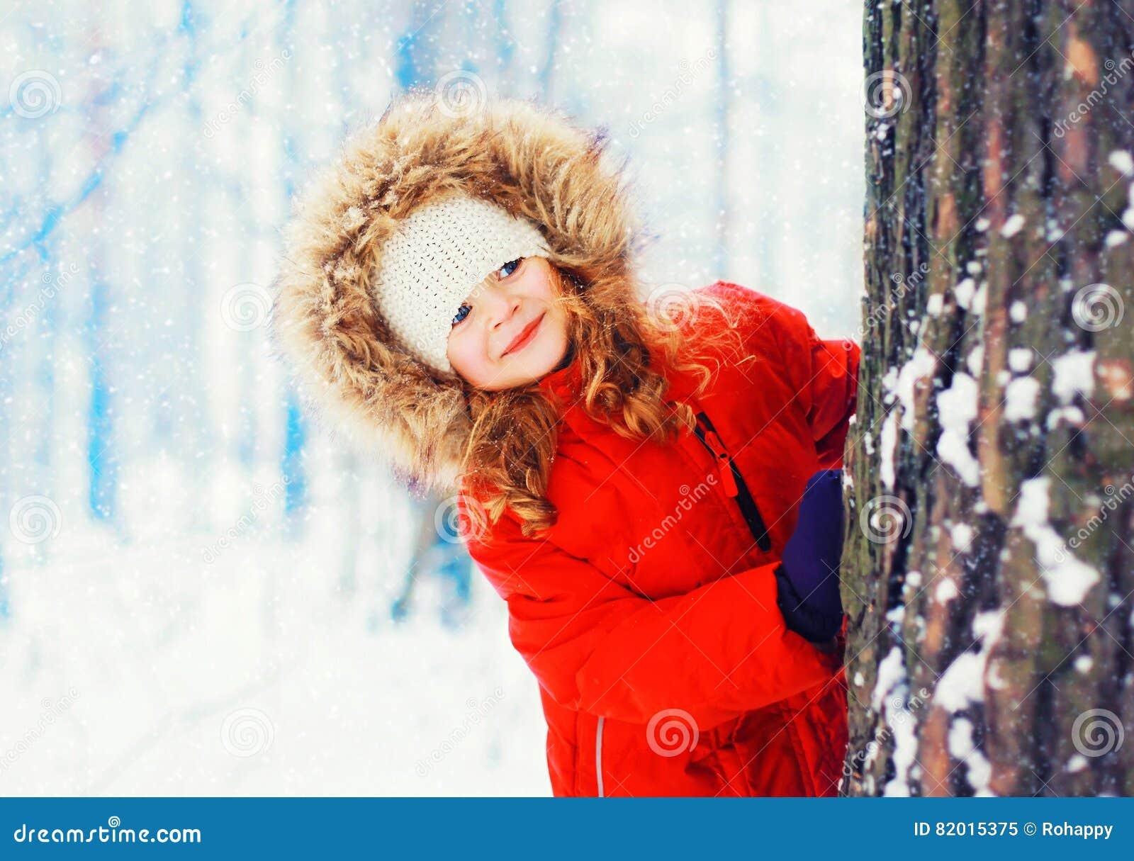 Niño sonriente feliz del retrato del invierno pequeño que juega cerca de árbol