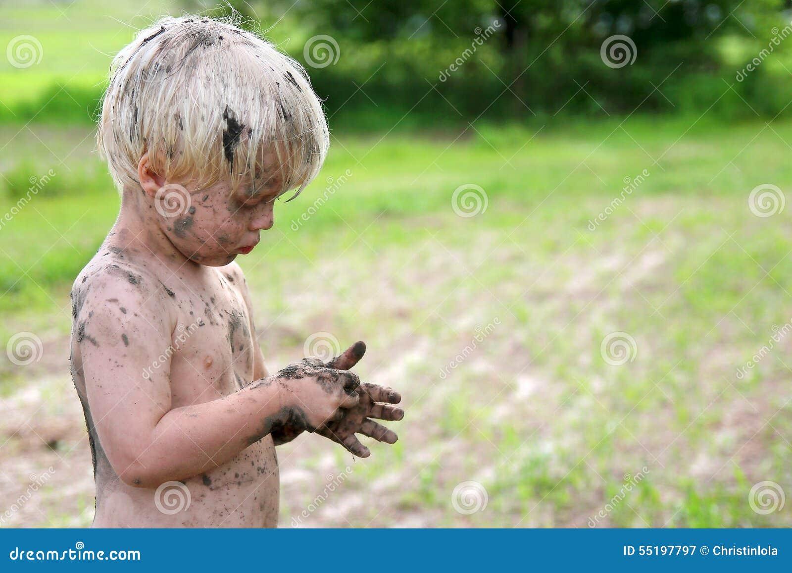 Niño sucio lindo que juega afuera en el país