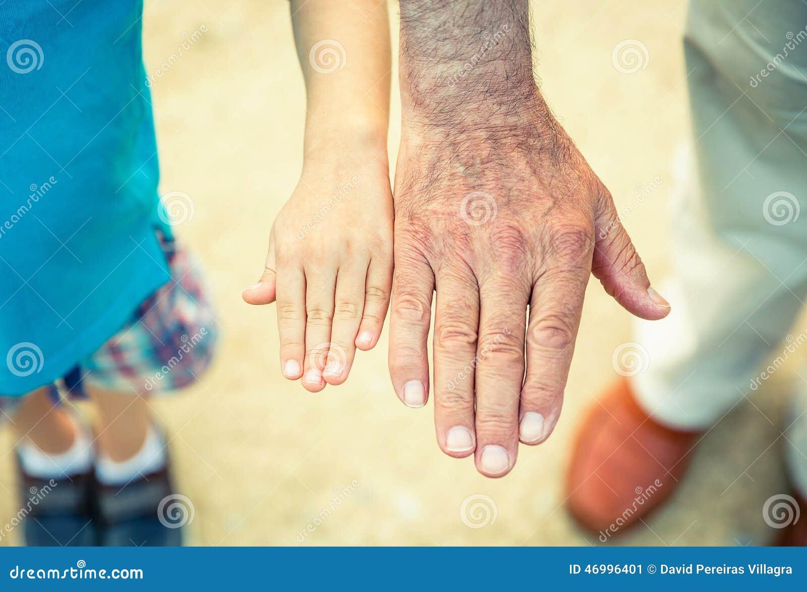 Niño y hombre mayor que comparan su tamaño de las manos