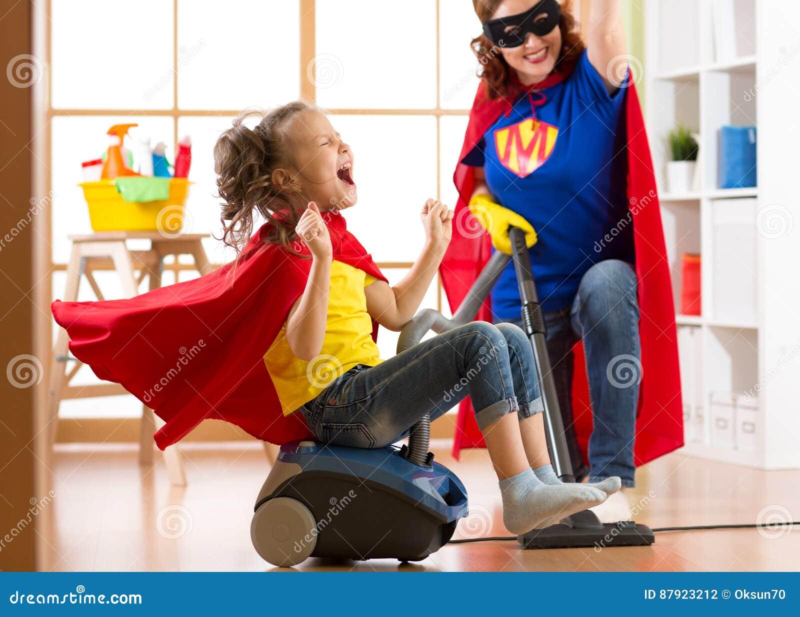 Niño y madre vestidos como super héroes que usan el aspirador en sitio La mujer y la hija de mediana edad de la familia se divier