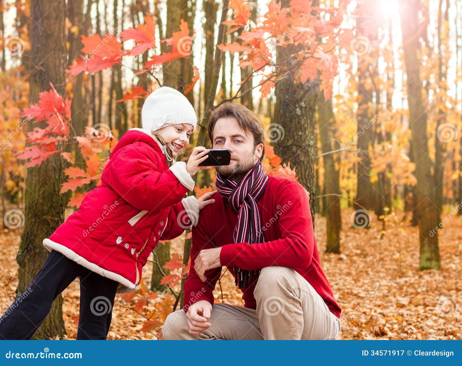 Niño y padre de la muchacha que toman la foto del otoño con el teléfono móvil