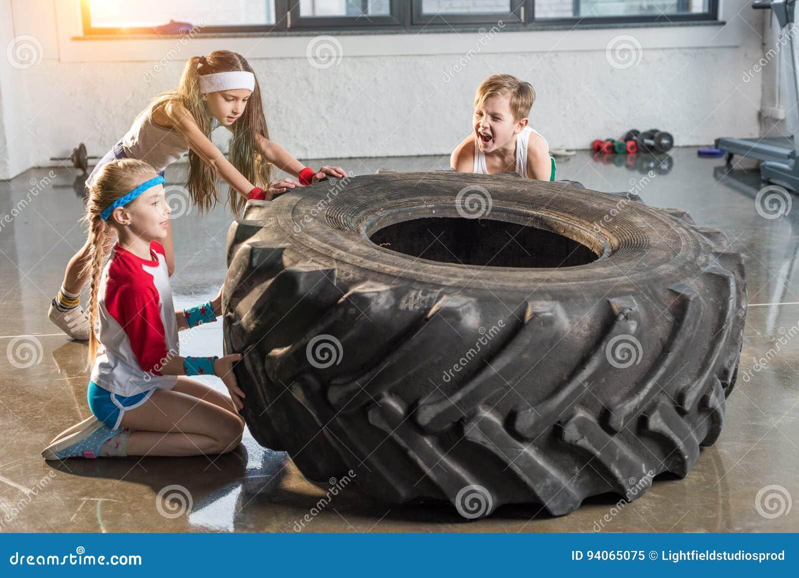 Niños adorables en el entrenamiento de la ropa de deportes con el neumático en el estudio de la aptitud