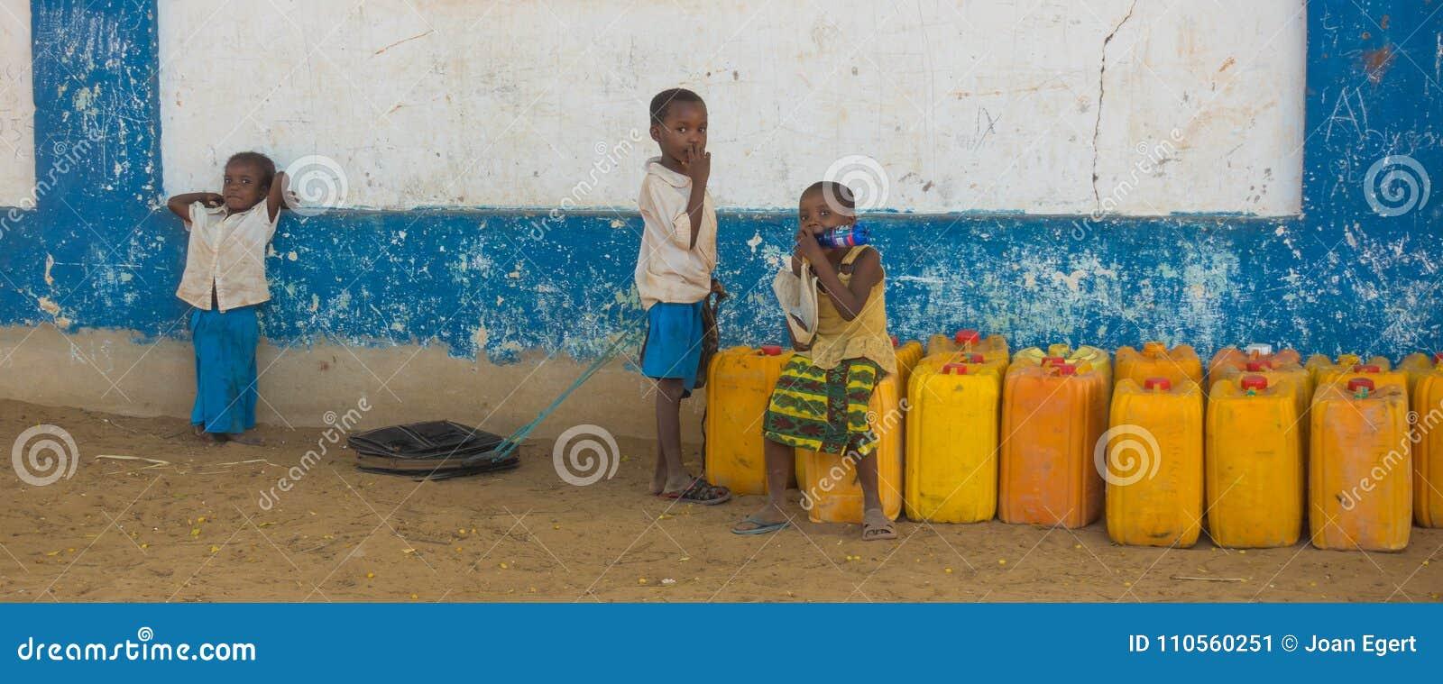 Niños africanos del pueblo en envases de la naranja de Kenia