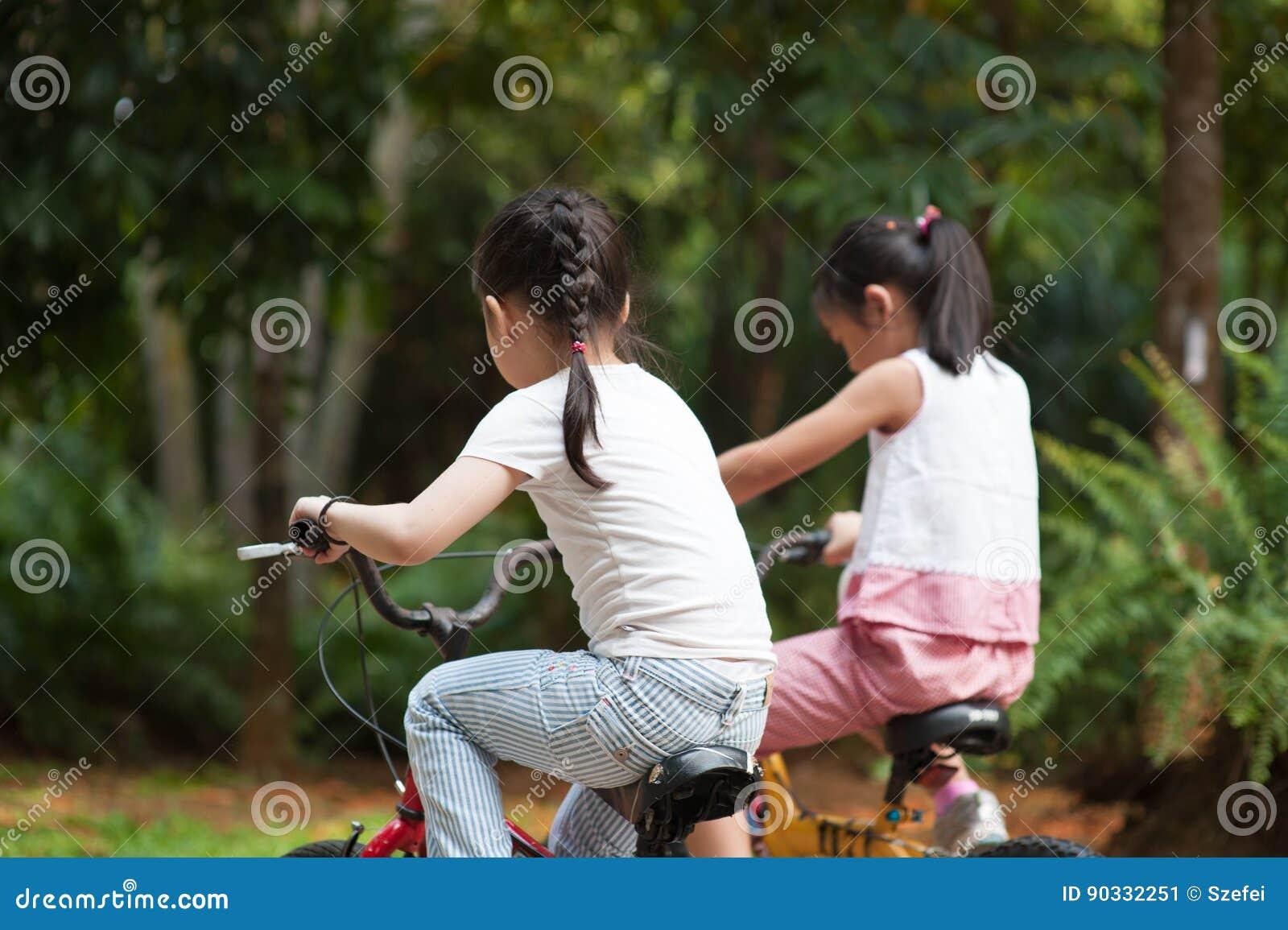 Niños asiáticos activos que montan la bicicleta al aire libre