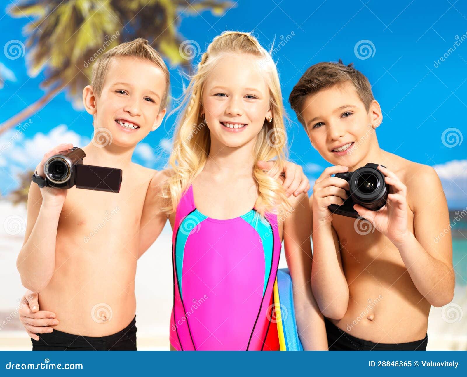 Niños con la cámara de vídeo del foto y en la playa.