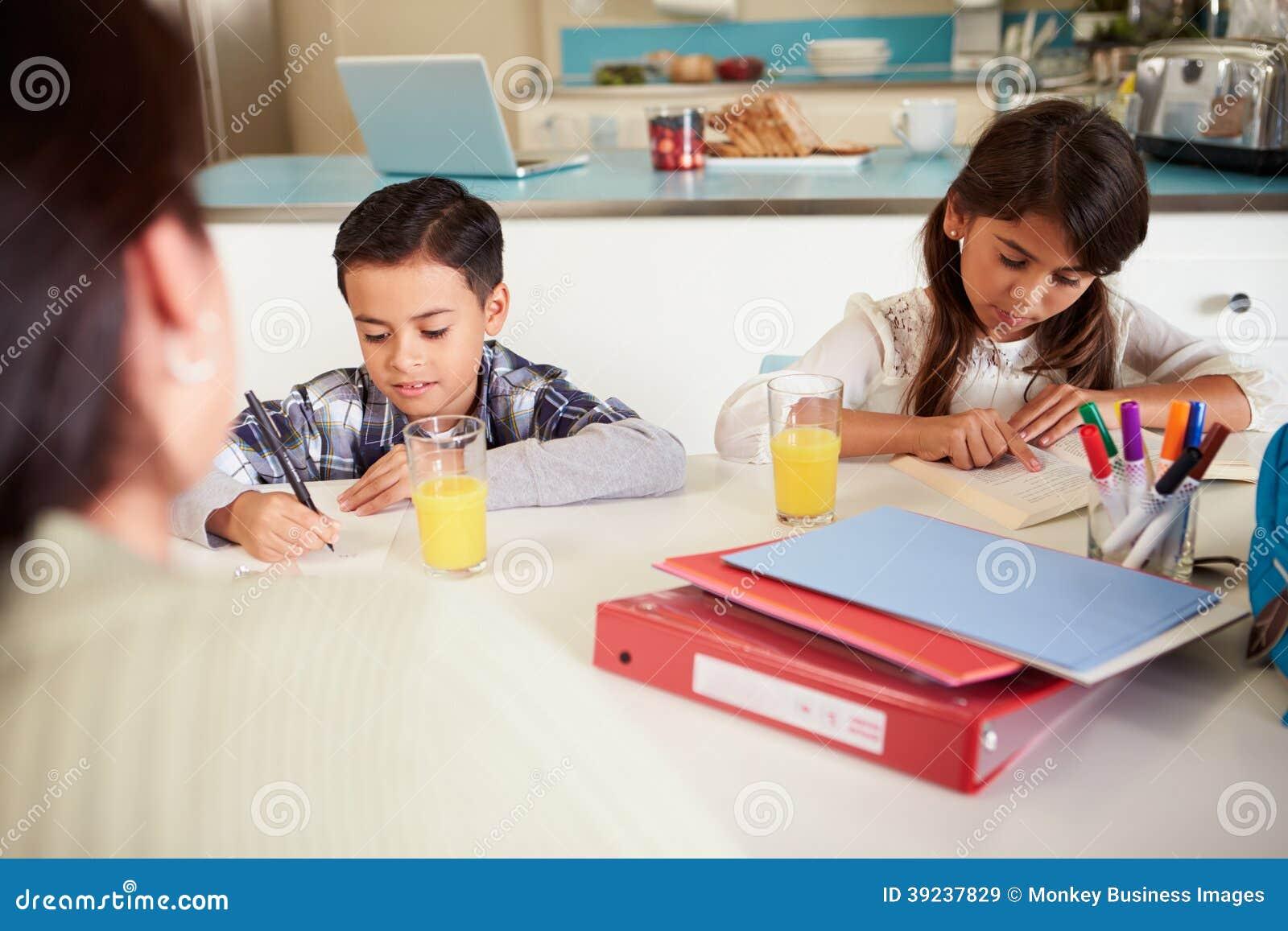 Niños de ayuda de la madre con la preparación en la tabla