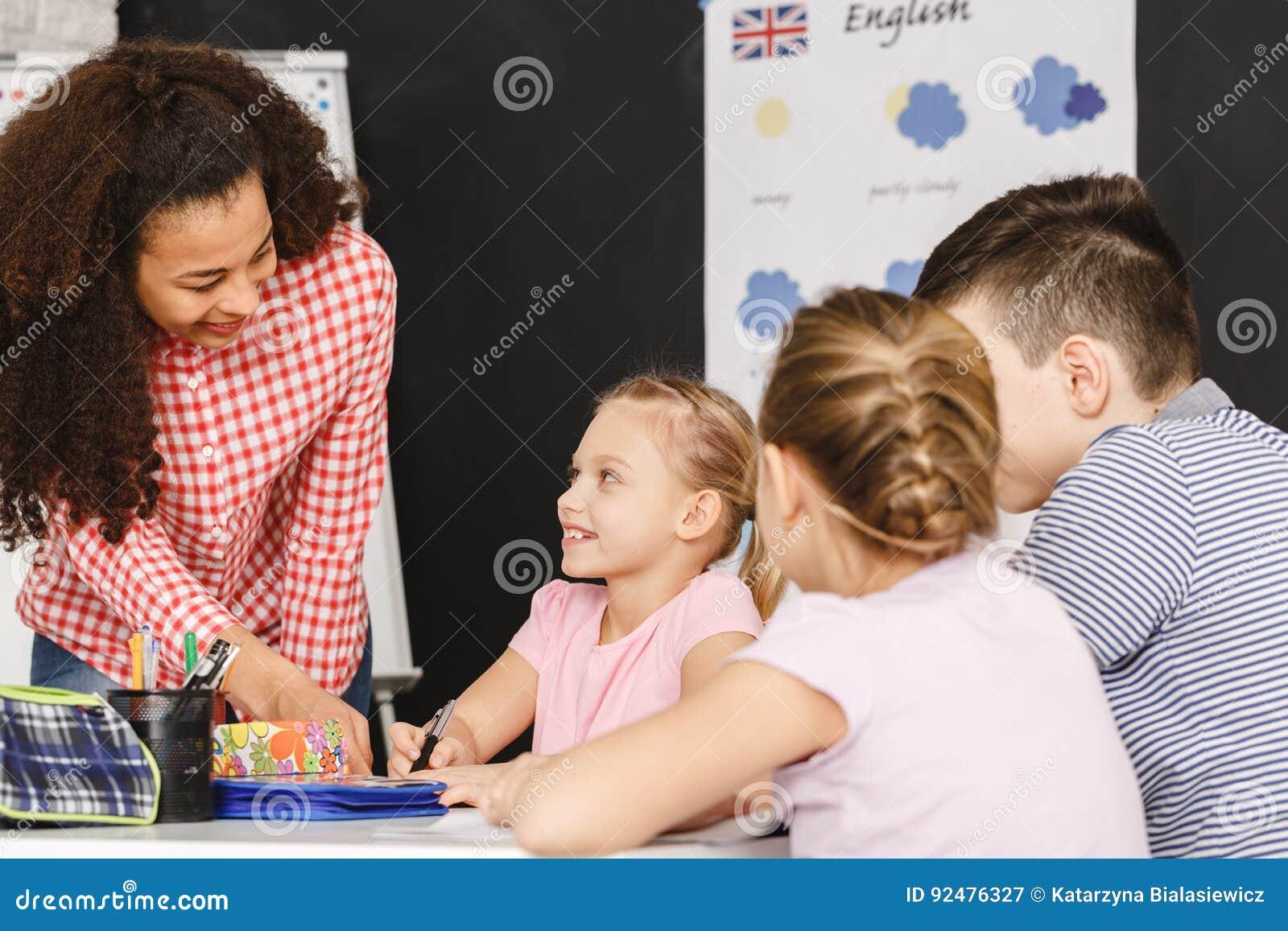 Niños de ayuda del profesor durante la lección