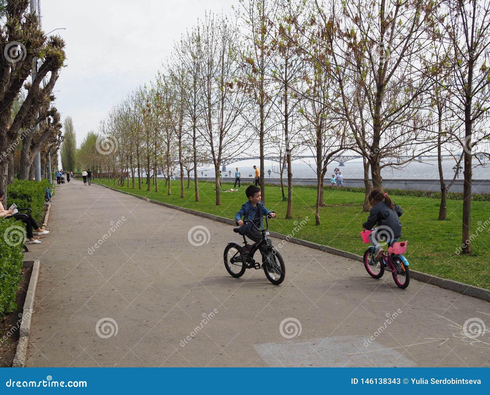 Niños de cinco años muchacho y bicicletas que montan de la muchacha El concepto de amistad r
