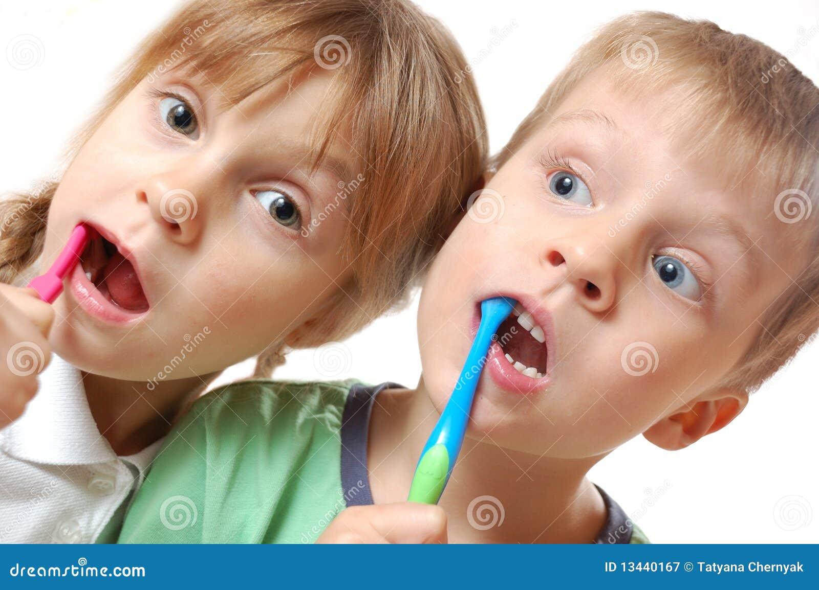 Niños de los dientes que aplican con brocha