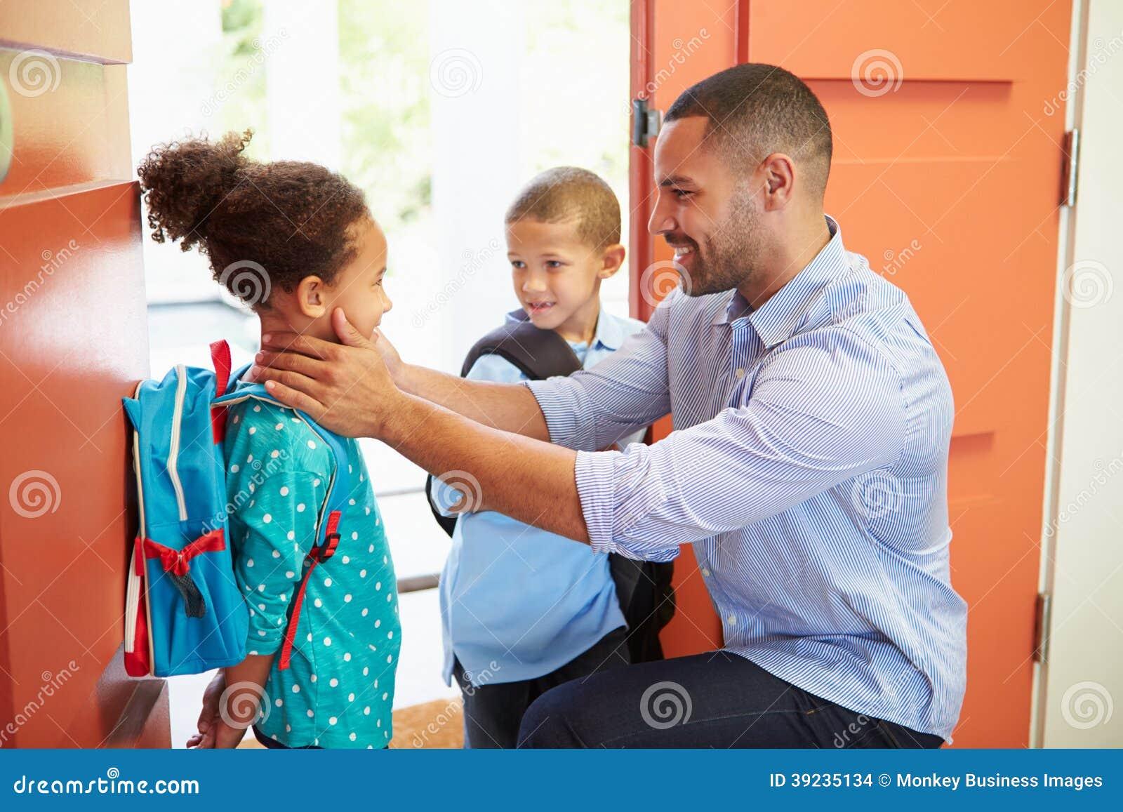 Niños de Saying Goodbye To del padre como se van para la escuela