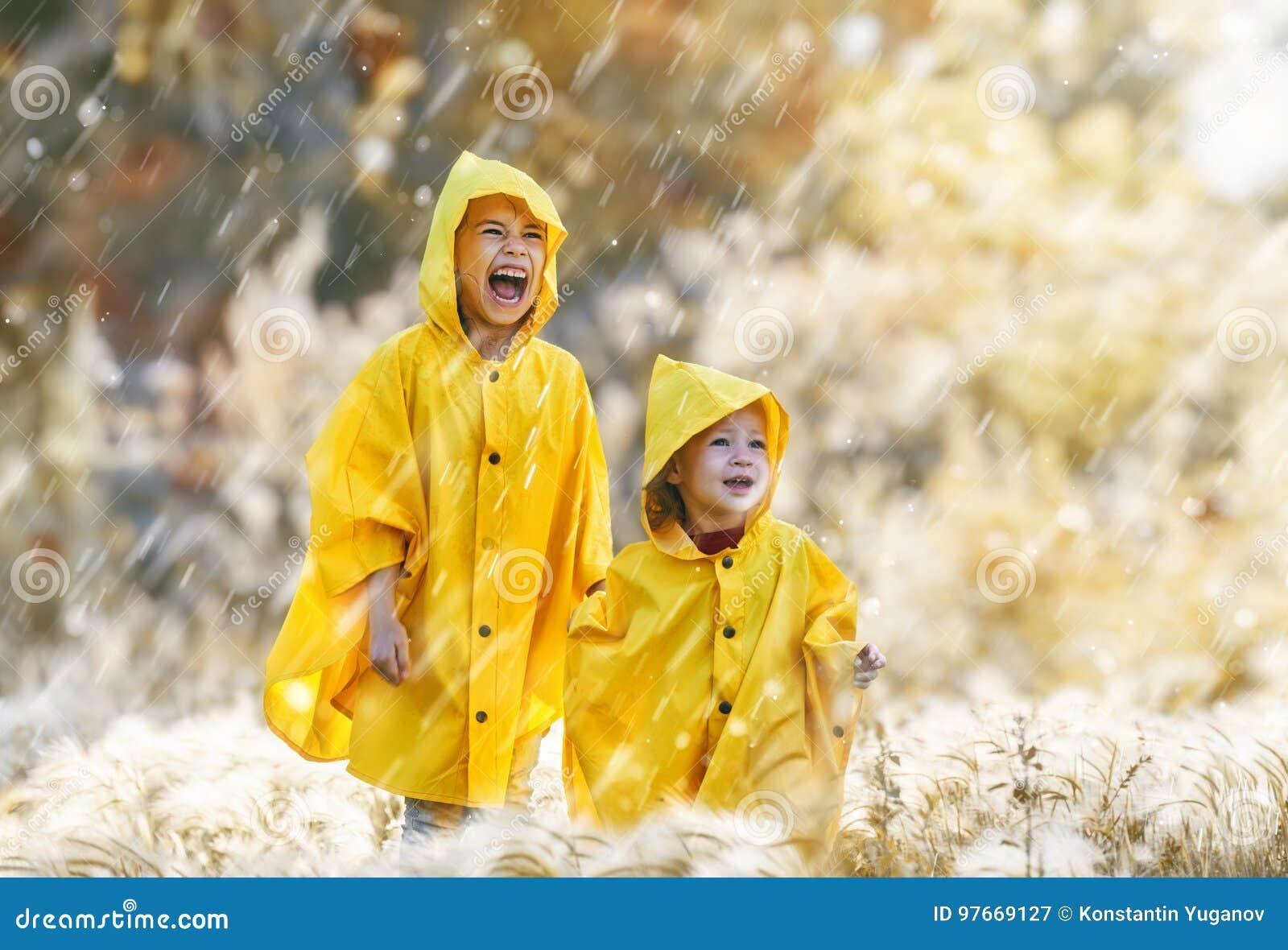 Niños debajo de la lluvia del otoño