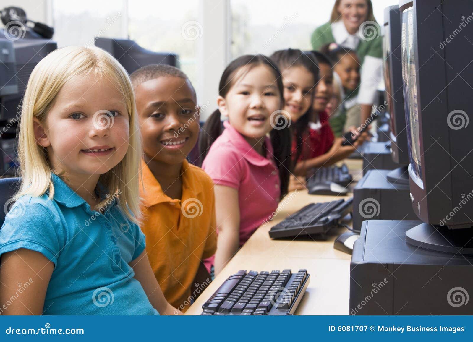 Niños del jardín de la infancia que aprenden utilizar los ordenadores