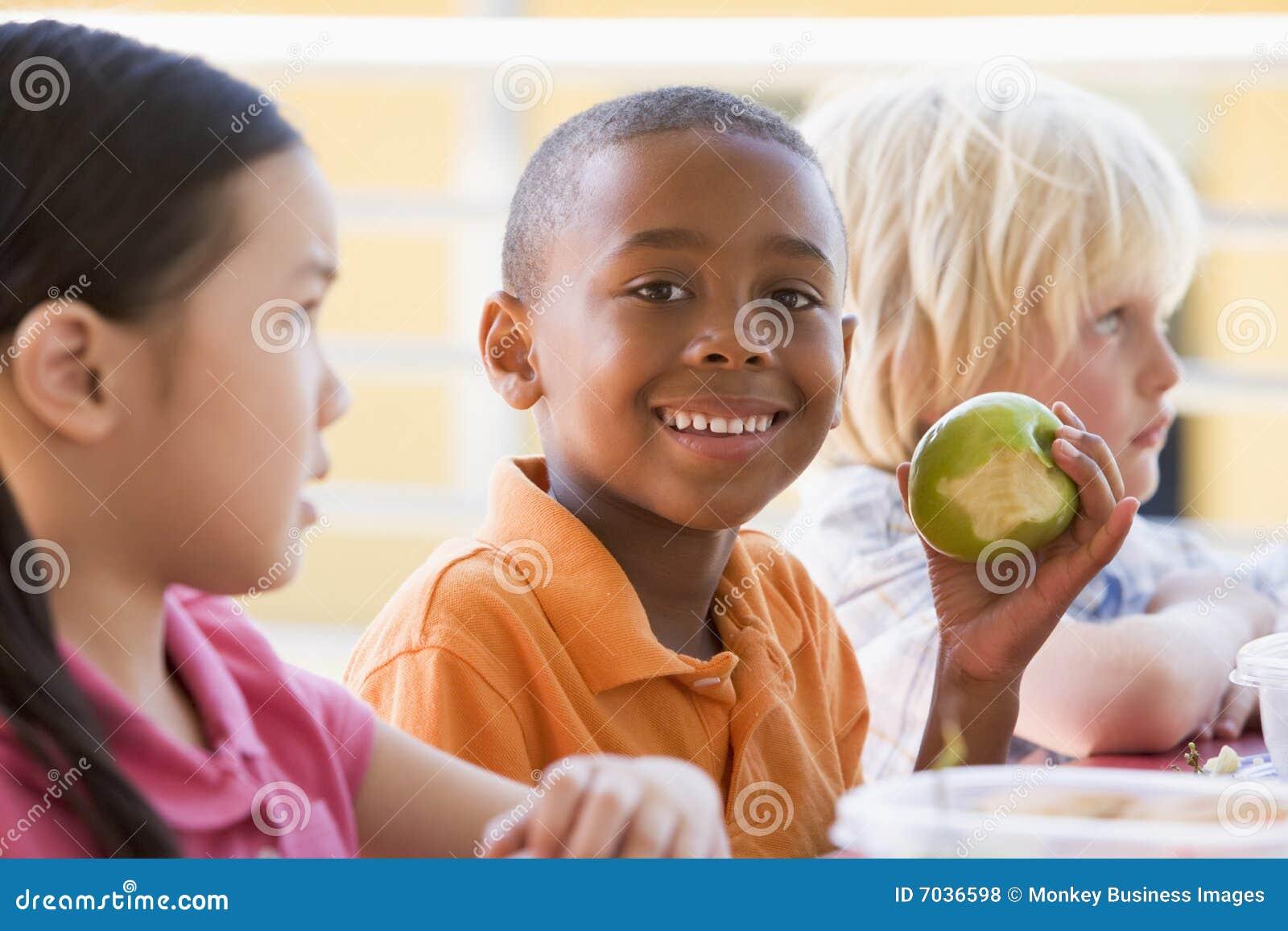Niños del jardín de la infancia que comen el almuerzo