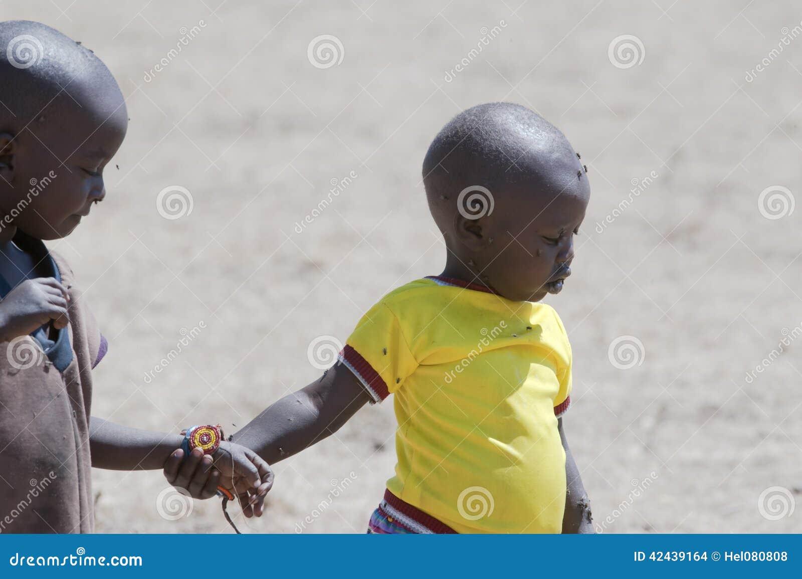 Niños del Masai por completo de moscas