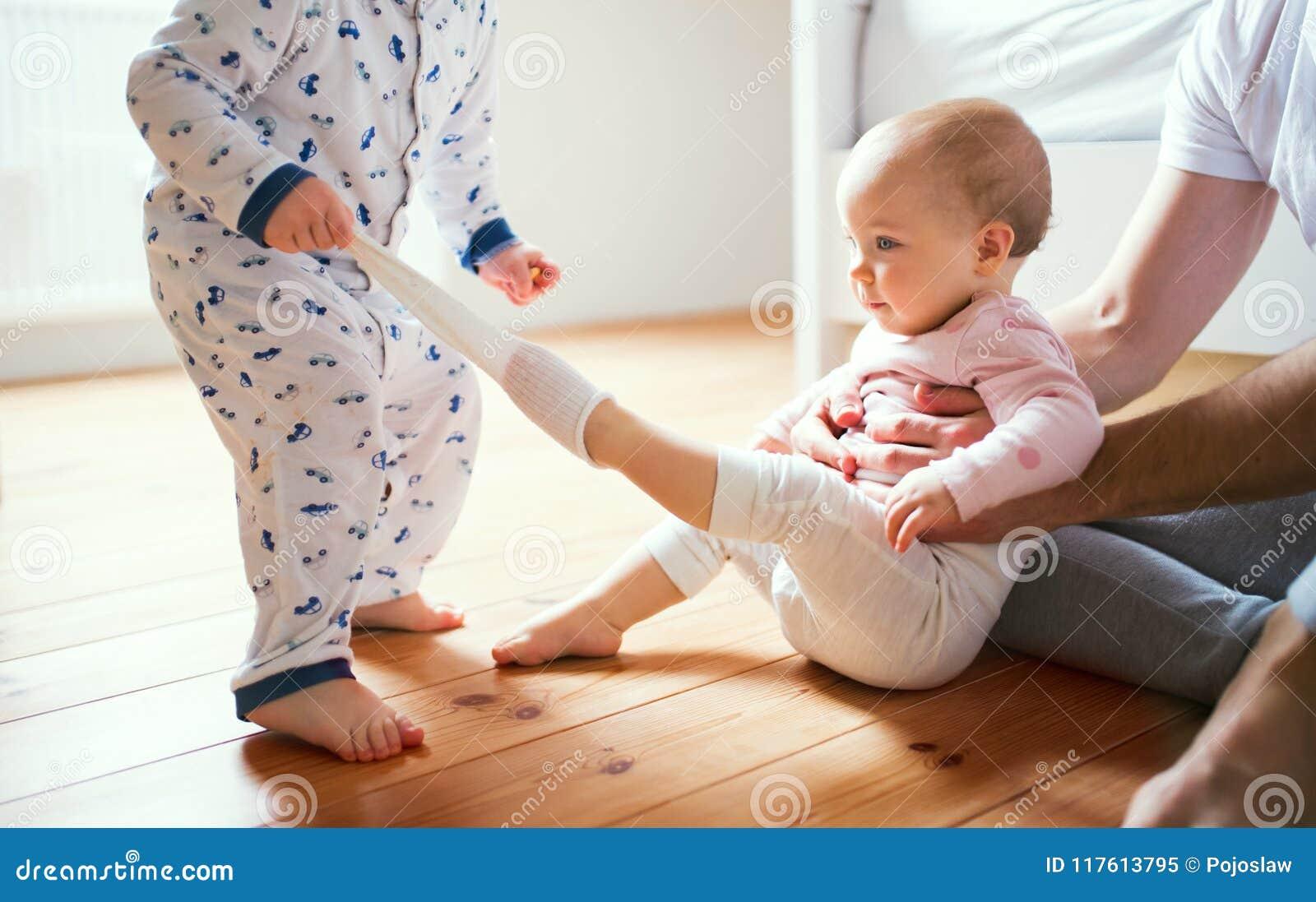 Niños del padre y del niño que se sientan en el piso en casa en la hora de acostarse