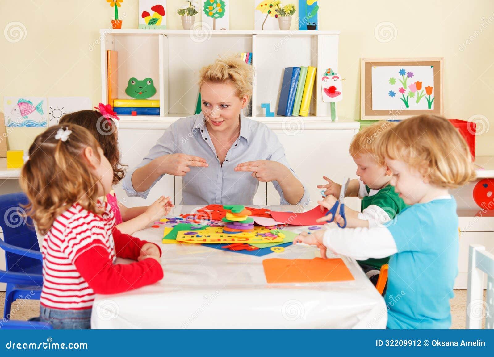 Niños del preescolar en la sala de clase con el profesor