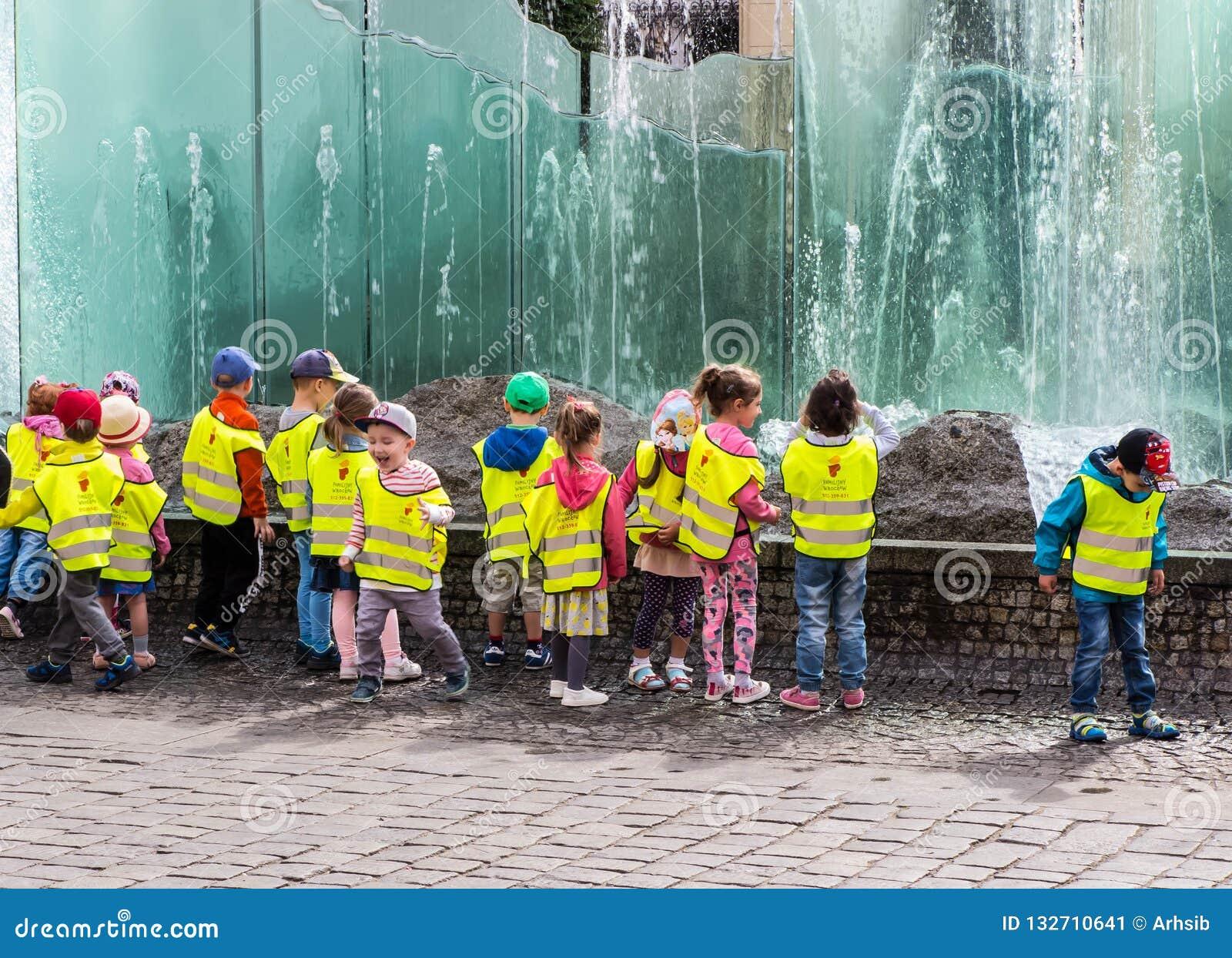 Niños divertidos en la fuente en Wroclaw