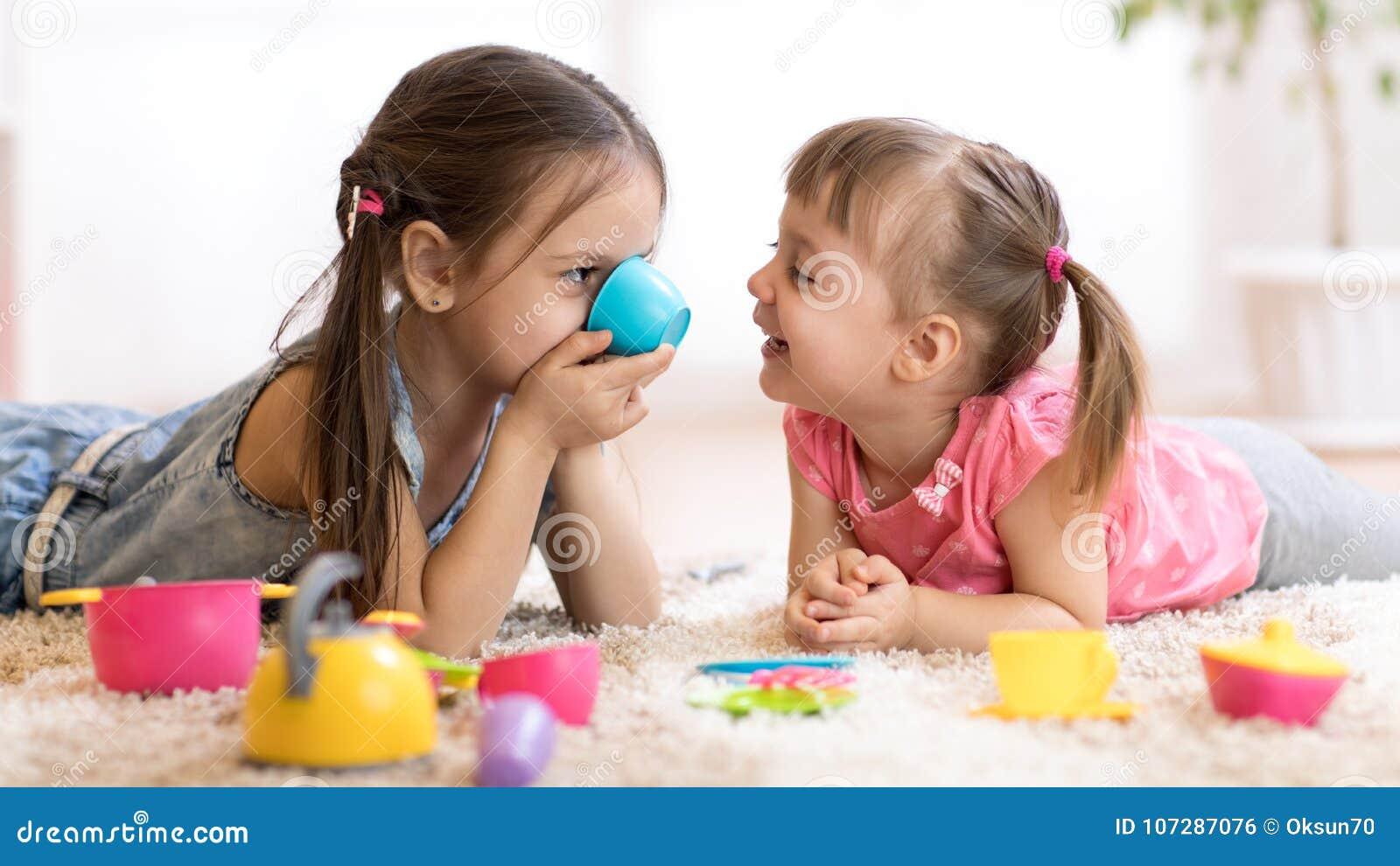 Niños divertidos lindos que juegan con los juguetes en casa