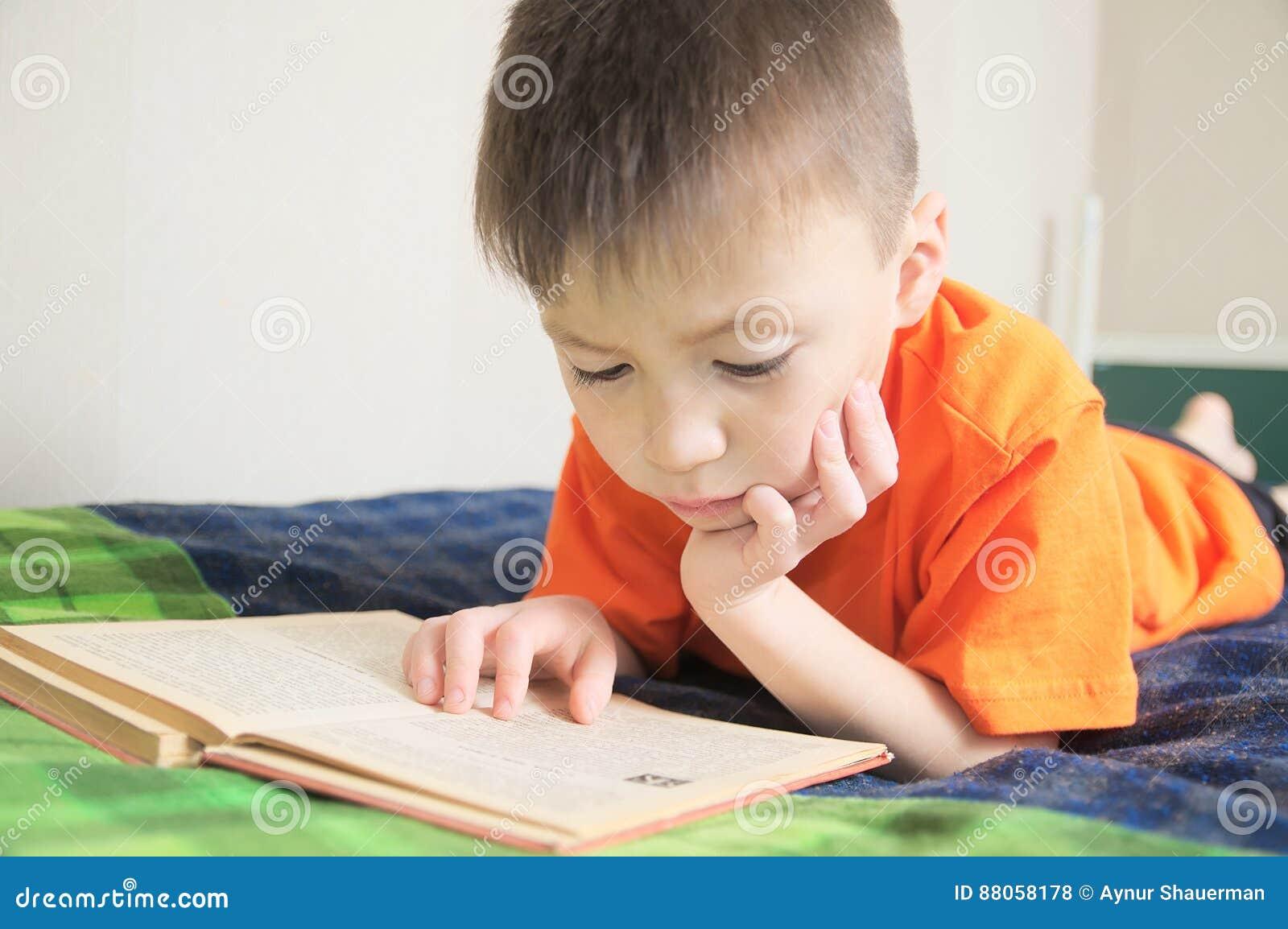 Niños educación, libro de lectura del muchacho que miente en la cama, retrato del niño que sonríe con el libro, educación, guión