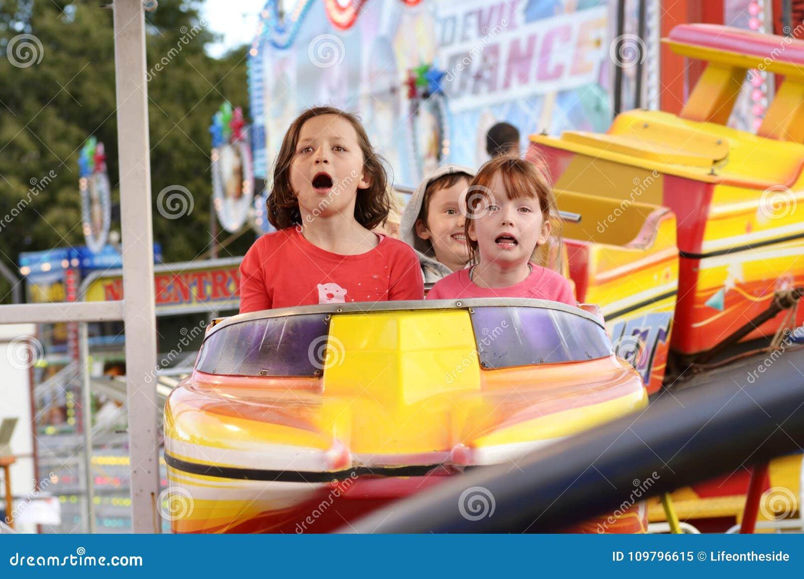 Niños emocionados que gritan en paseo de la montaña rusa del carnaval