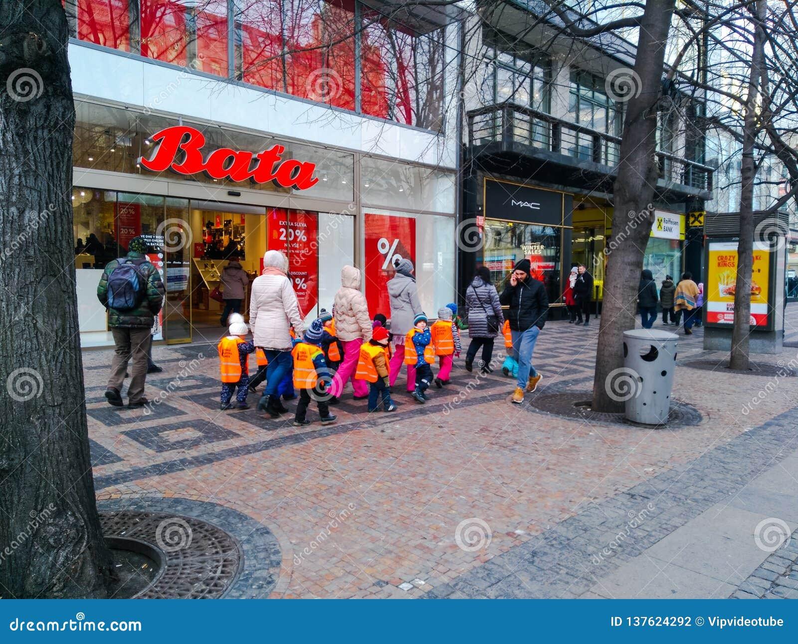 Niños en chalecos anaranjados que caminan en el centro de Praga