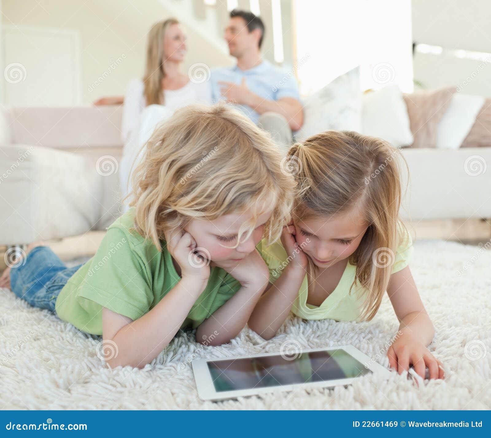 Niños en el piso con la tableta y los padres detrás de ellos