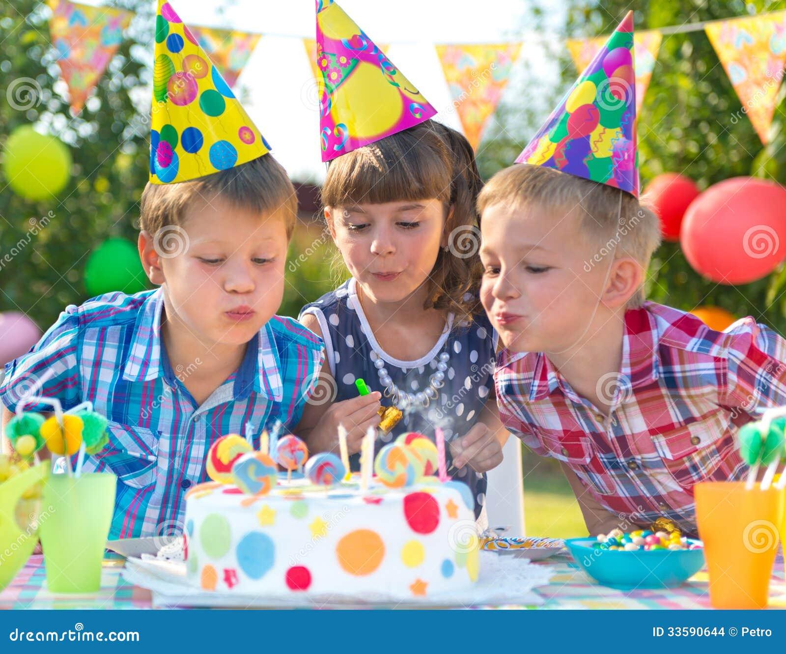 Niños en las velas que soplan de la fiesta de cumpleaños en la torta